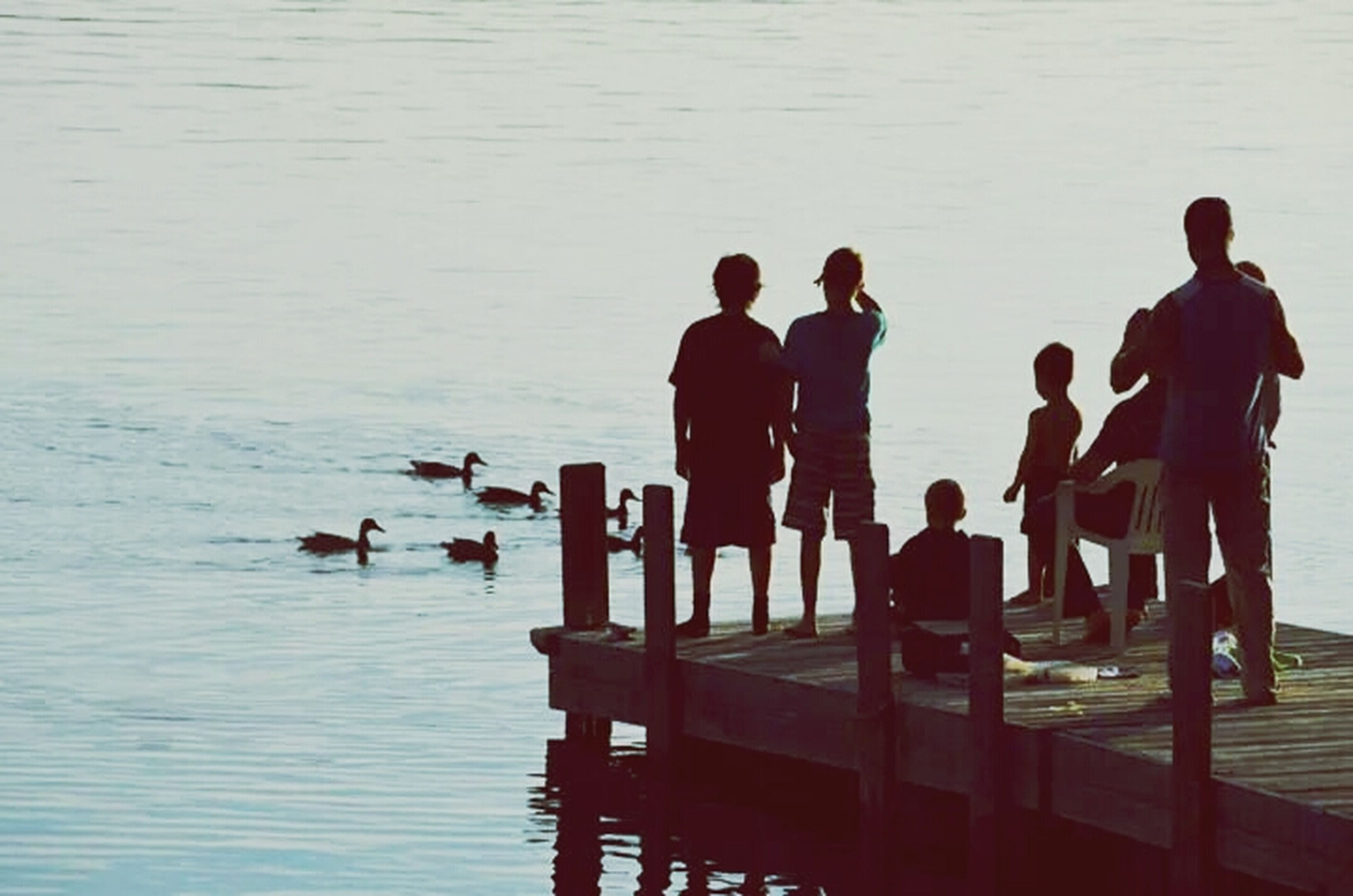 water, men, lifestyles, togetherness, leisure activity, person, silhouette, sea, standing, sitting, friendship, medium group of people, lake, pier, large group of people, reflection, vacations