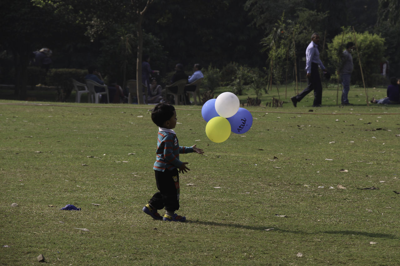boys, childhood, playing, leisure activity, real people, full length, grass, field, ball, green color, rear view, day, standing, balloon, men, two people, outdoors, soccer, togetherness, lifestyles, child, nature, tree, people, adult