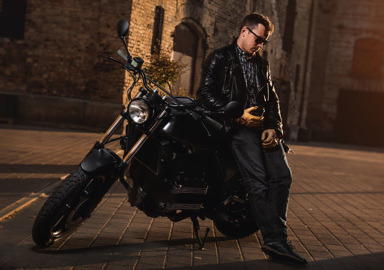 Man with a cafe-racer motorcycle outdoors 60s Adult Bike Biker Cafe Racer Motorcycles Cafe-racer Coffee Custom Bikes Full Length Handsome Leather Jacket Male Man Motorbike Motorcycle Motorcyclist Outdoors People Retro Styled Riding Street Subculture Transportation Vehicle Vintage