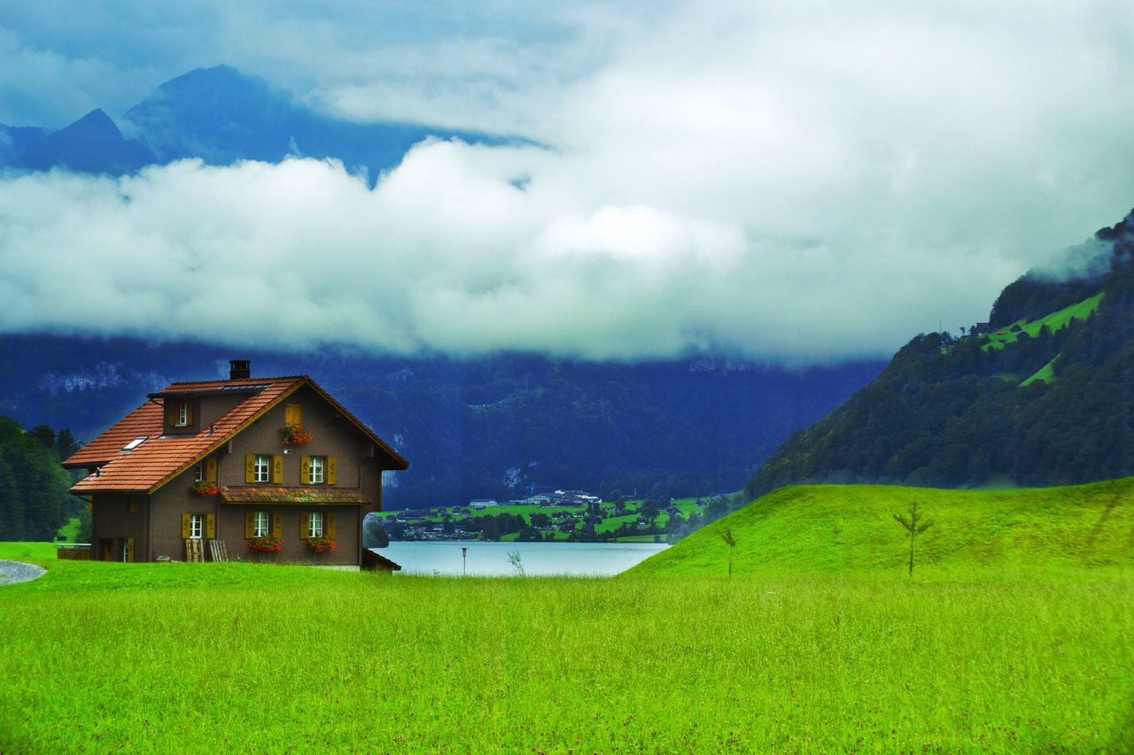 Country house on landscape against clouds