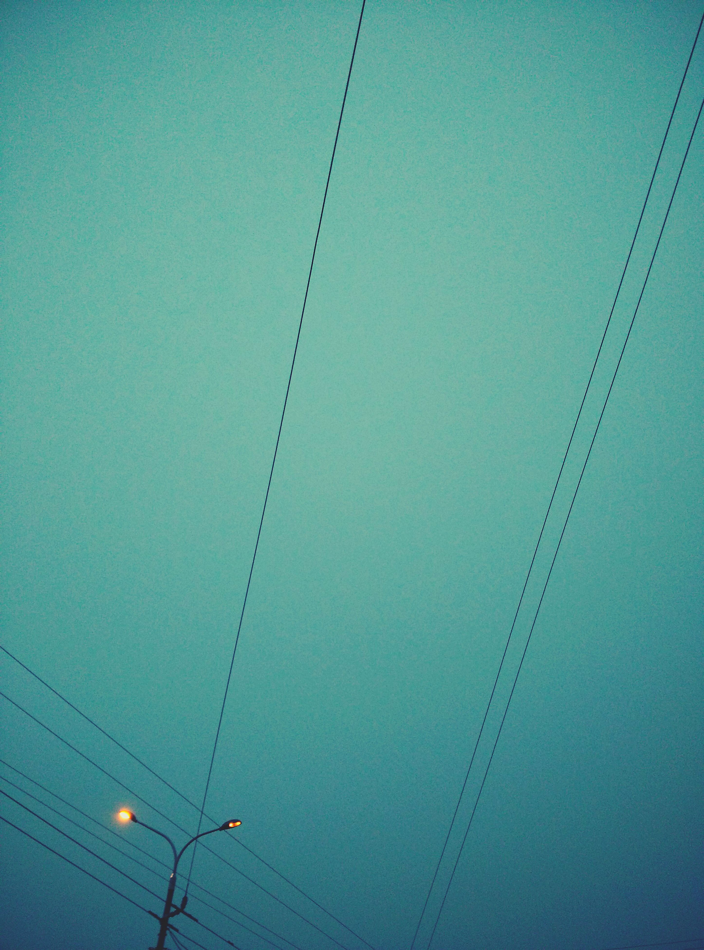 low angle view, electricity, power line, connection, cable, power supply, clear sky, technology, copy space, fuel and power generation, lighting equipment, electricity pylon, blue, no people, built structure, outdoors, hanging, ceiling, sky, architecture