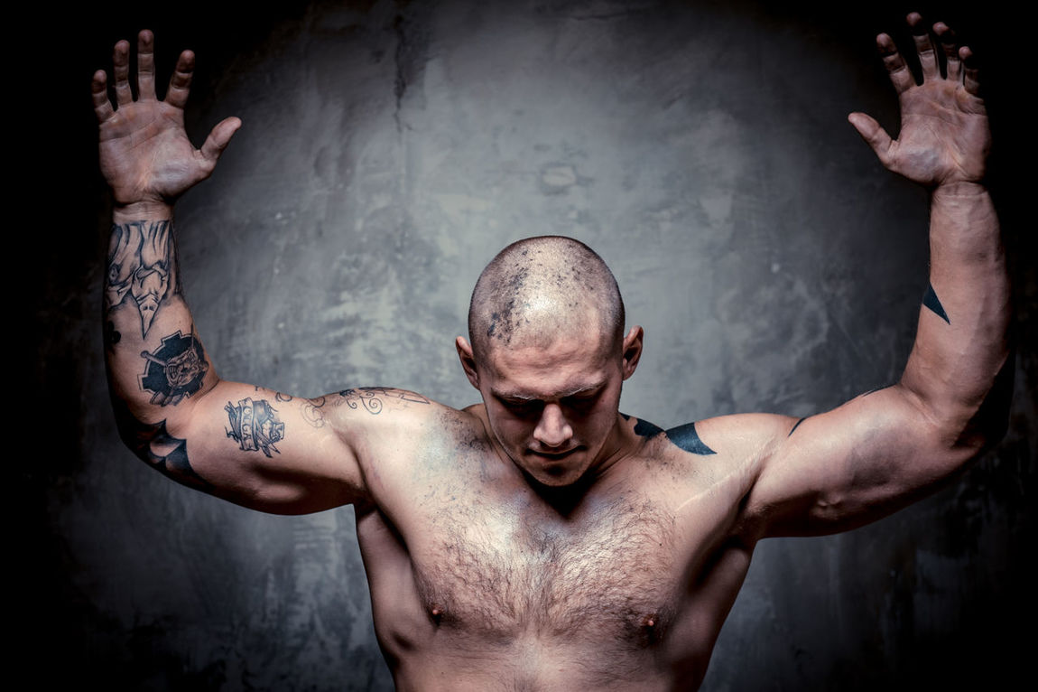 Muscular tattooed man with hands raised up posing over grey background Adults Only Athlete Athletic BodyBuilder Bodybuilding Caucasian Criminal Hands Up Handsome Hooligan Male Man Masculinity Muscle Muscular Build Only Men Shaven Head Sport Sportive Sportsmen Strength Strong Studio Shot Tattoed Tattoo