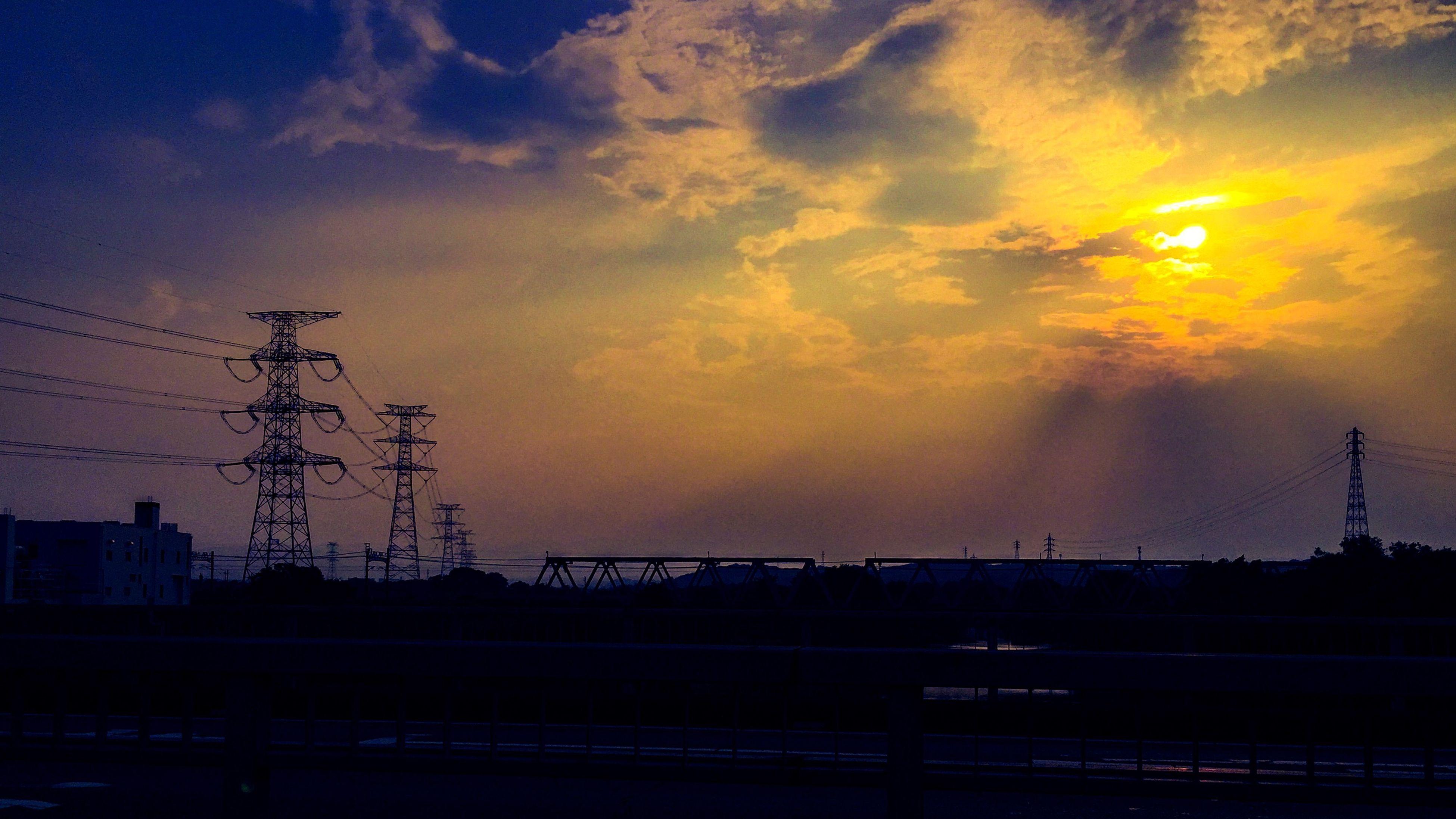 Electricity Pylon On Landscape Against Sunset Sky