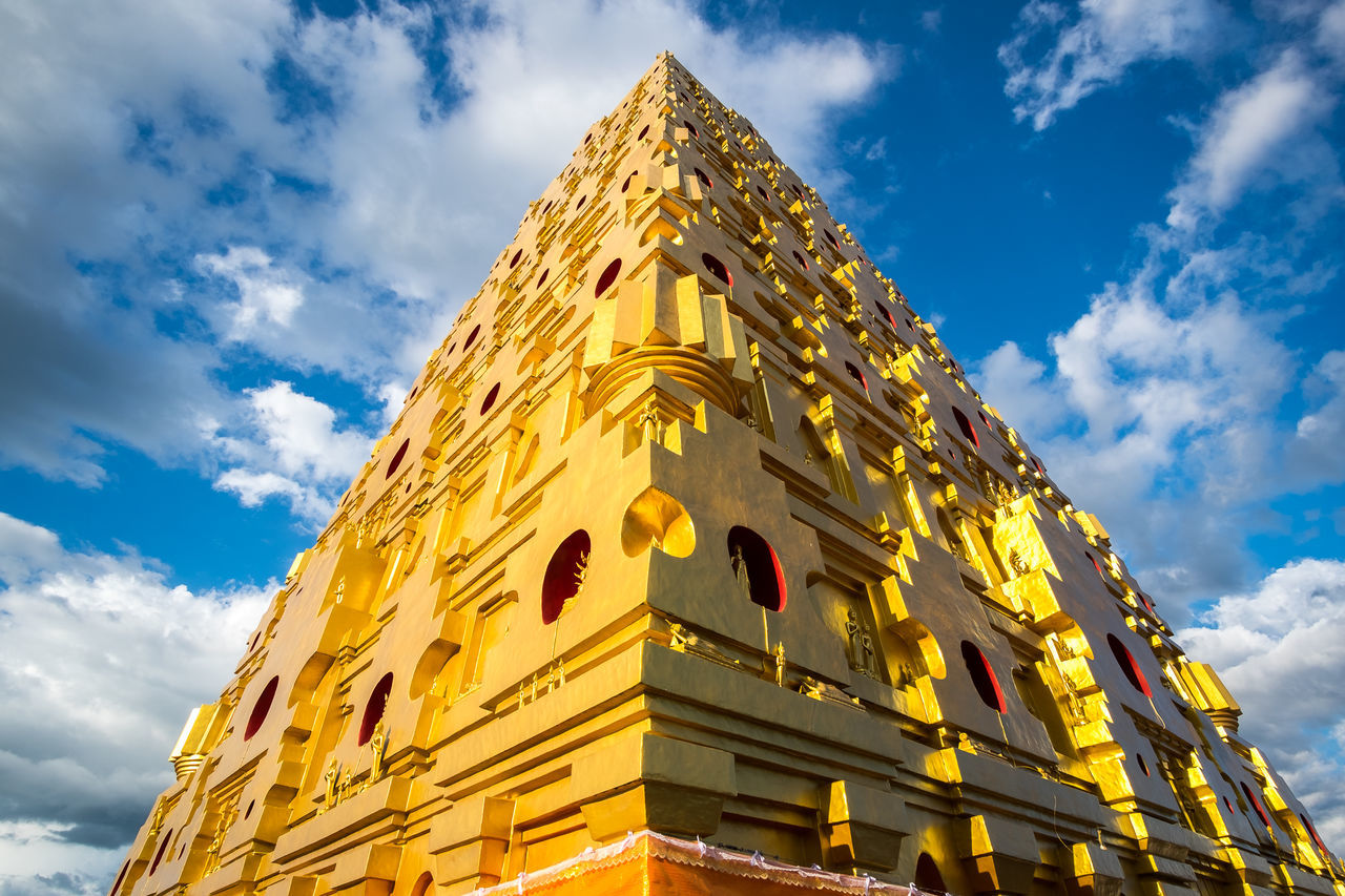 low angle view, cloud - sky, sky, architecture, built structure, day, yellow, history, spirituality, building exterior, gold colored, religion, outdoors, place of worship, no people