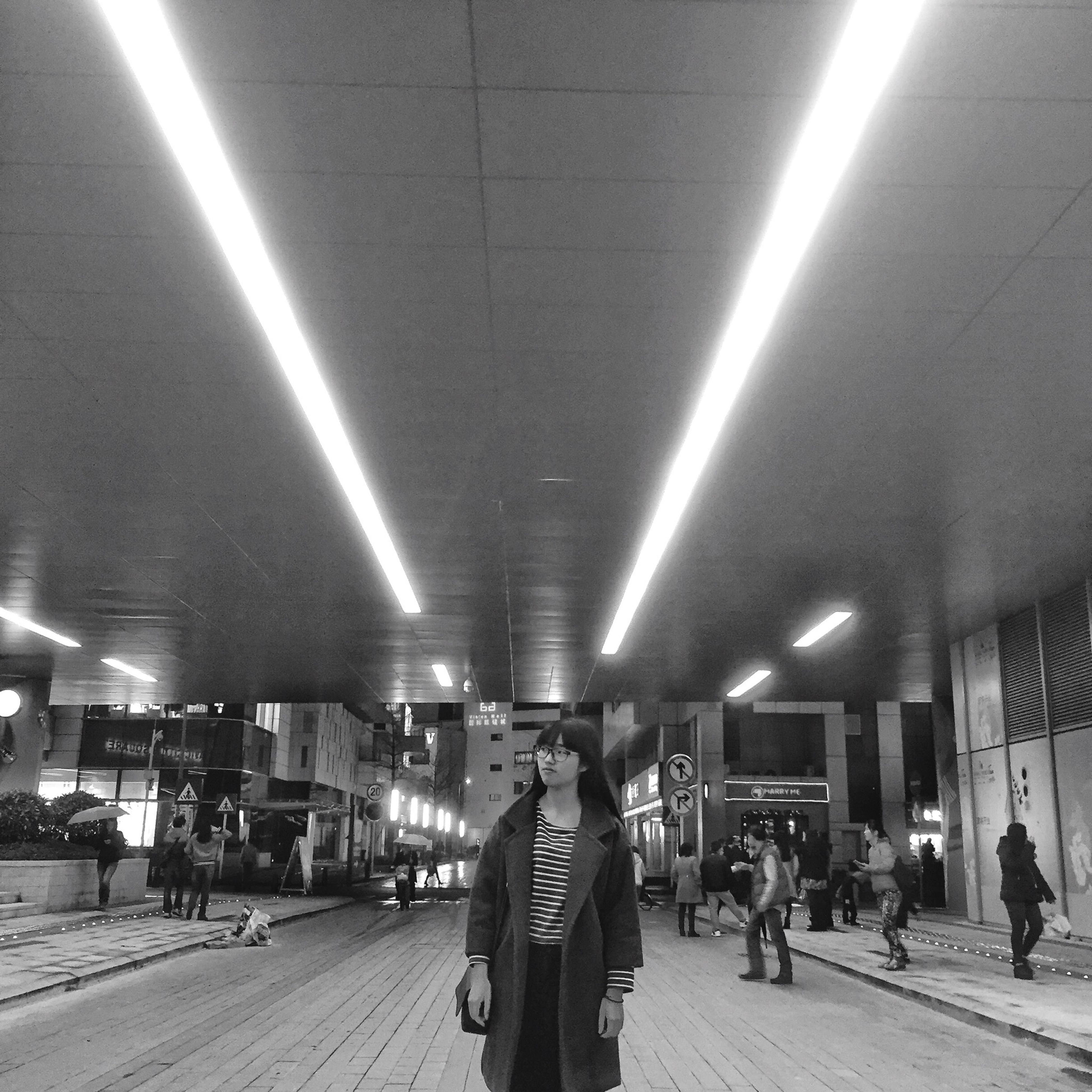 lifestyles, men, illuminated, person, large group of people, walking, leisure activity, architecture, built structure, city life, indoors, transportation, city, full length, ceiling, street, lighting equipment, night, railroad station