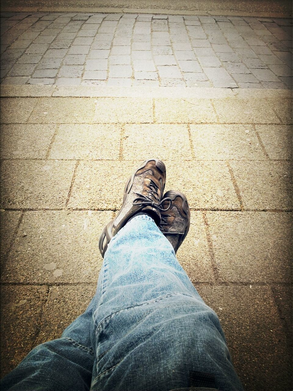 Low Section Of Man Sitting On Sidewalk