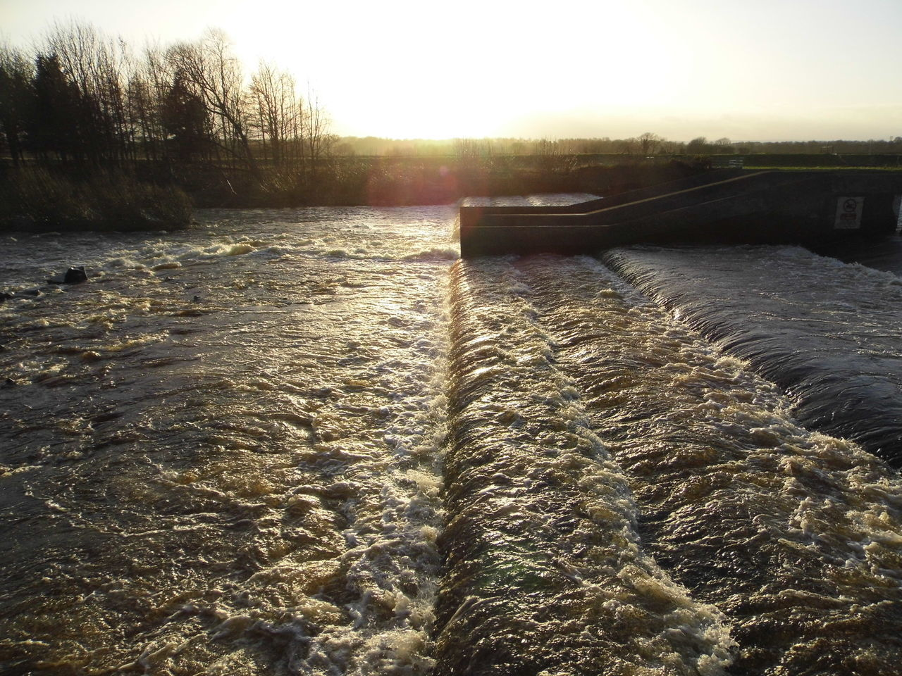 Flowing River In Canal Against Sky During Sunset
