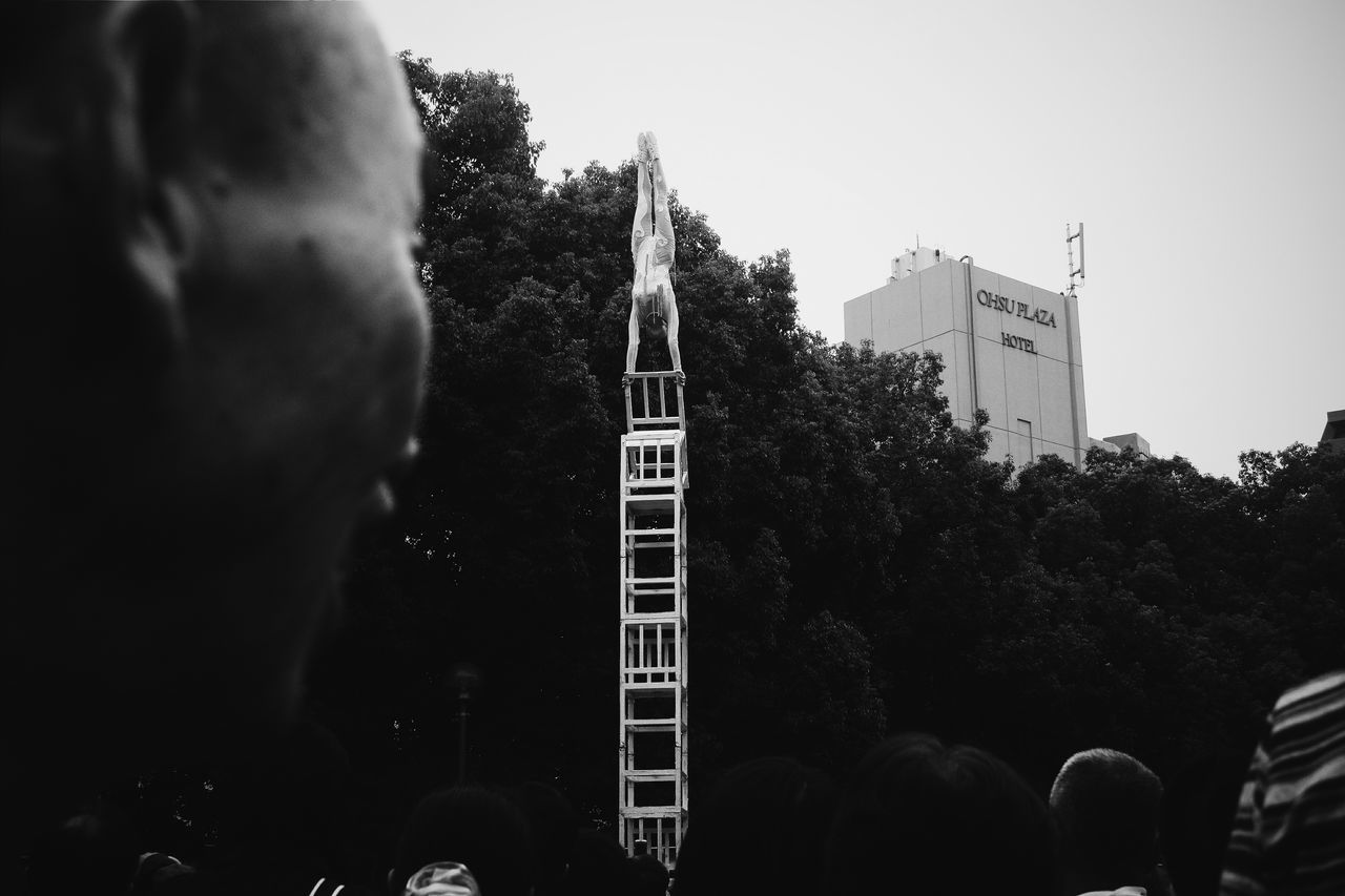 A girl balances atop a stack of chairs at the Osu Street Performing Festival in Nagoya City, Japan. Adventure ASIA Backpacking Black And White City Life Japan Outdoors Perspective Travel Travel Destinations Traveling