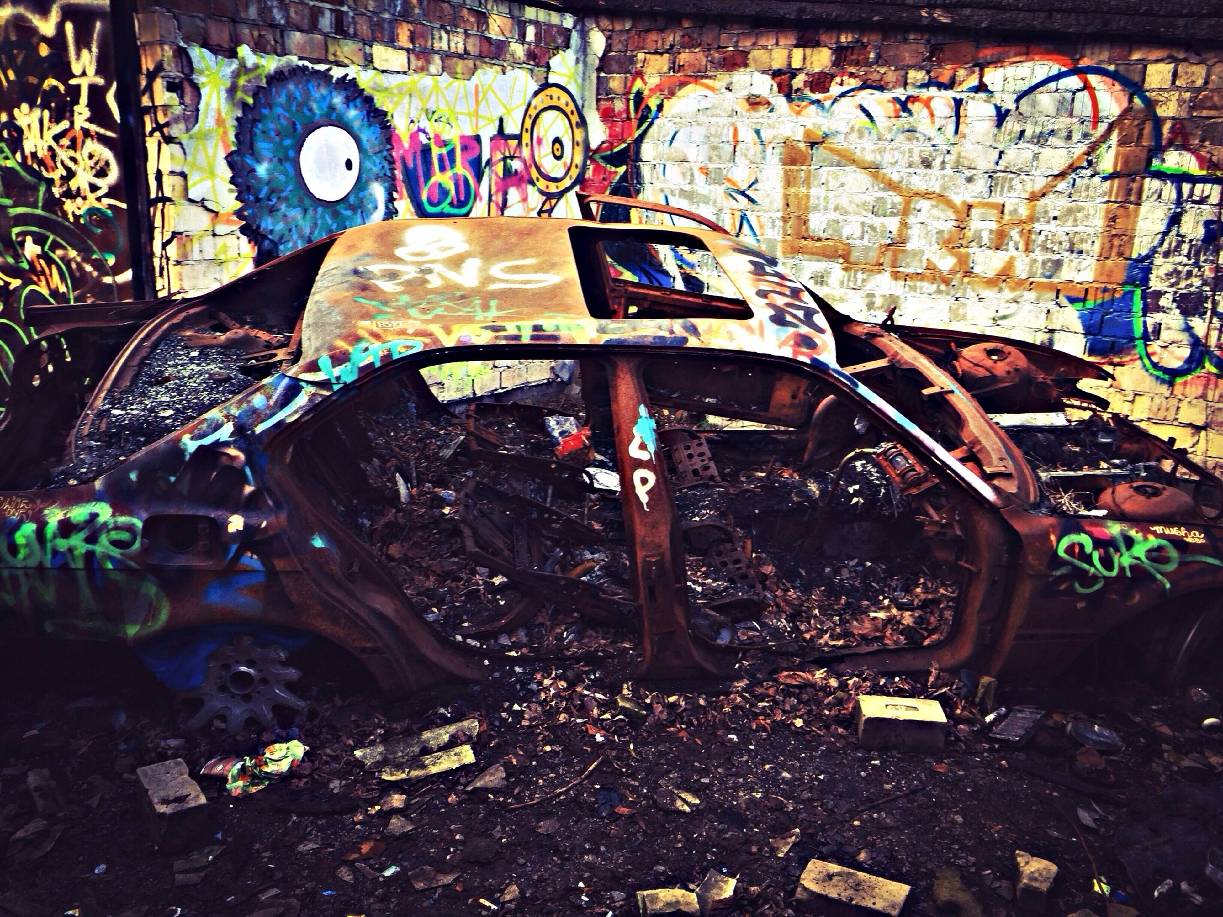 abandoned, high angle view, obsolete, land vehicle, large group of objects, abundance, built structure, messy, architecture, indoors, transportation, day, damaged, auto post production filter, old, graffiti, mode of transport, no people, chair
