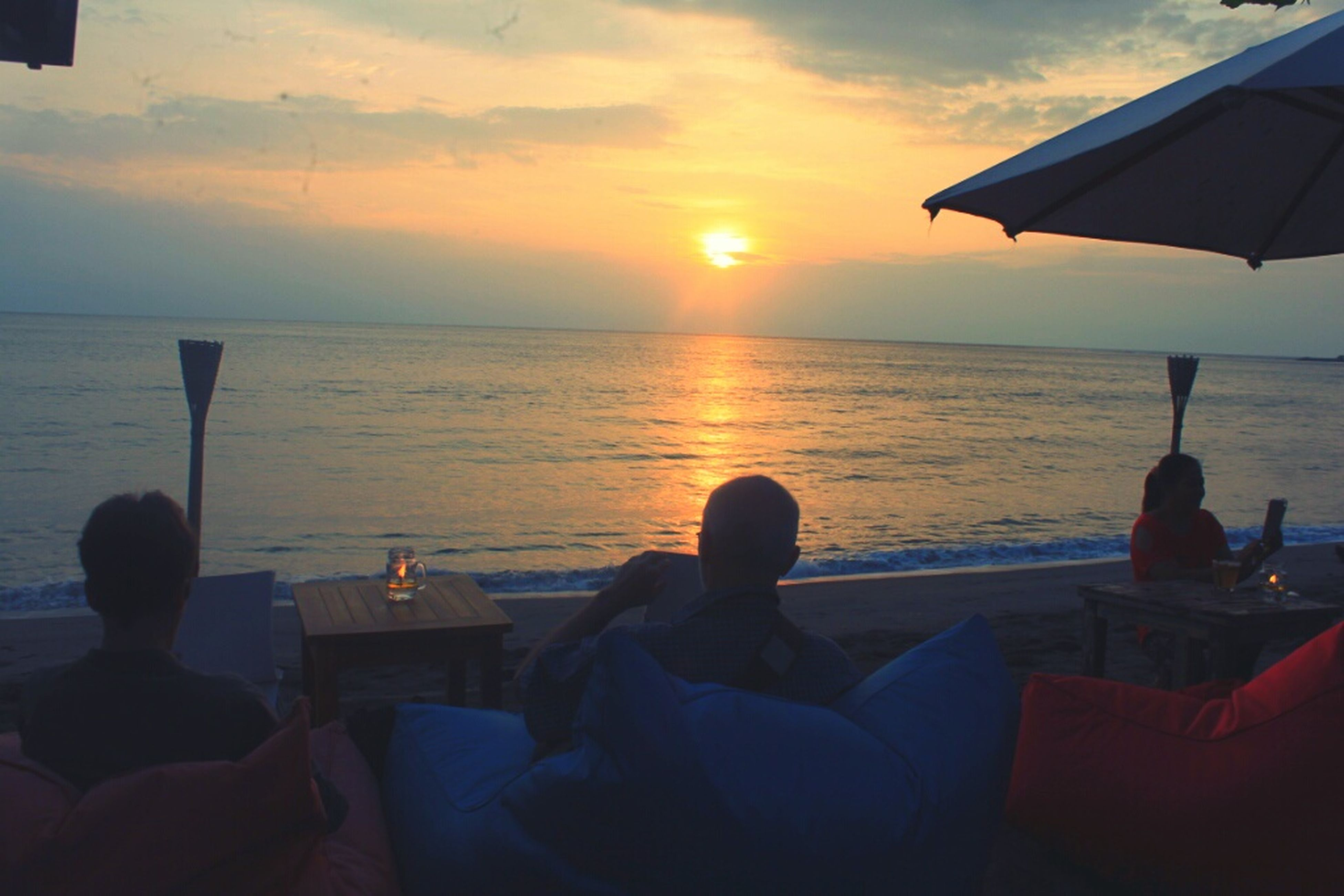 sea, horizon over water, water, sunset, sky, chair, sun, relaxation, scenics, lifestyles, sitting, vacations, person, leisure activity, beach, tranquil scene, beauty in nature, men, restaurant