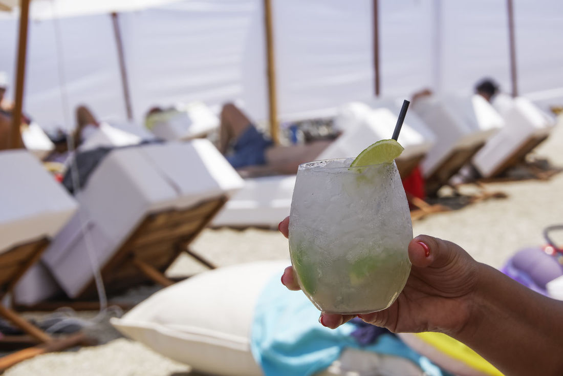 Cocktail drink in hand with blurred beach background. Female hand holding an iced glass of Caipirinha alcoholic cocktail with sliced lime, on a sunny day. Alcohilism Alcohol Alcoholic  Beach Beach Cocktail Beach Fun Beach Holiday Blurred Background Blurred Beach Caipirinha Cocktail Deck Chair Drink Drink Beach Sweat Sand Enjoyment Glass Hand Iced Glass Lime Refreshment Relaxation SLICE Summer Summer Drink Travel