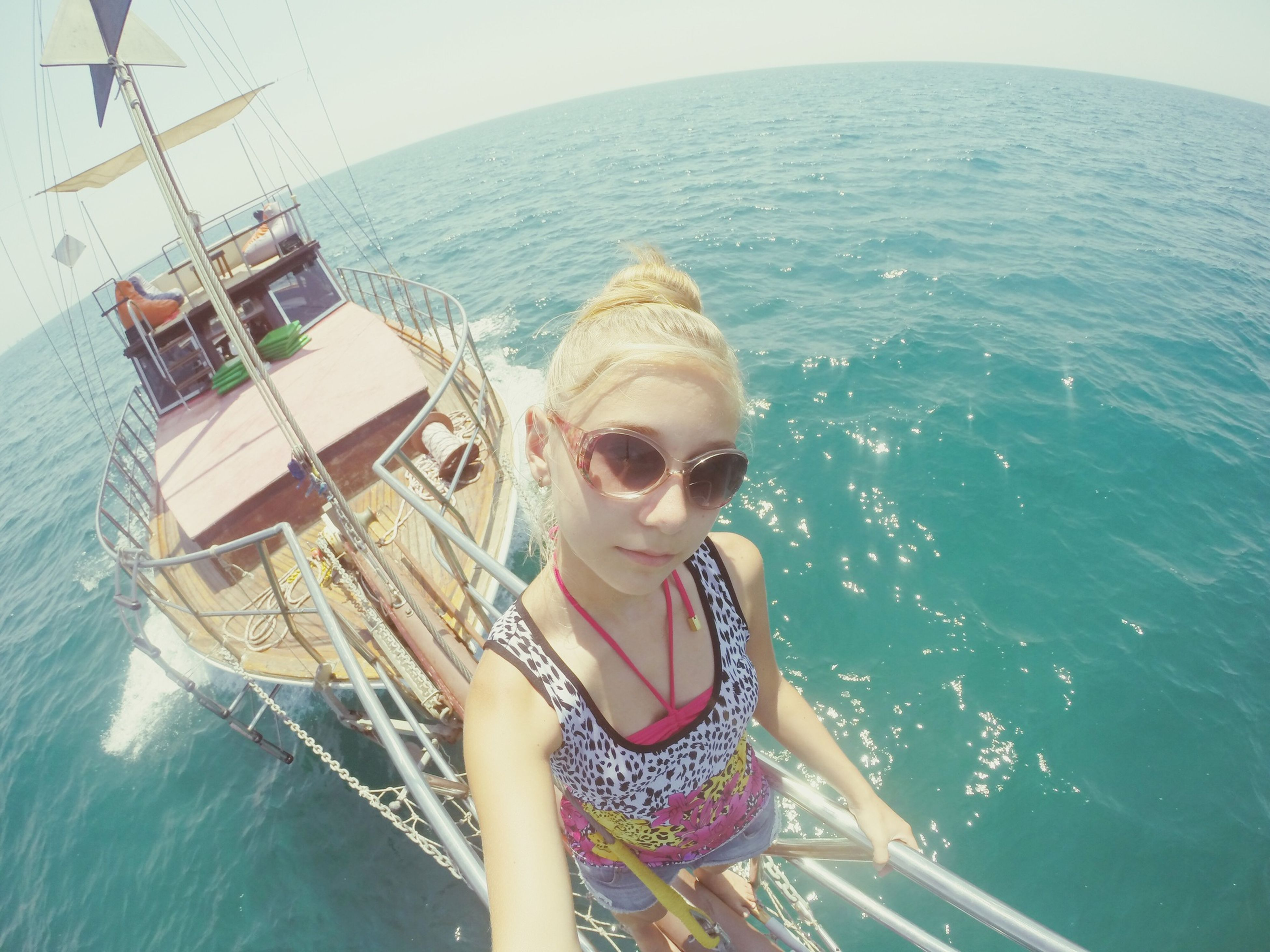 water, lifestyles, sea, leisure activity, young adult, person, casual clothing, young women, nautical vessel, portrait, looking at camera, vacations, standing, day, blue, three quarter length, sunglasses, transportation