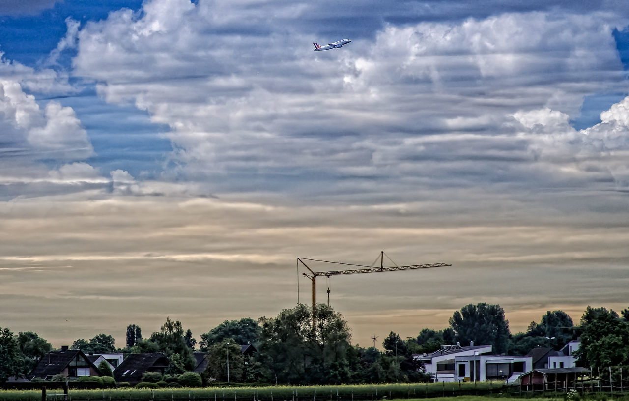 cloud - sky, sky, outdoors, flying, no people, architecture, sunset, nature, built structure, day, beauty in nature, tree, windmill, industrial windmill