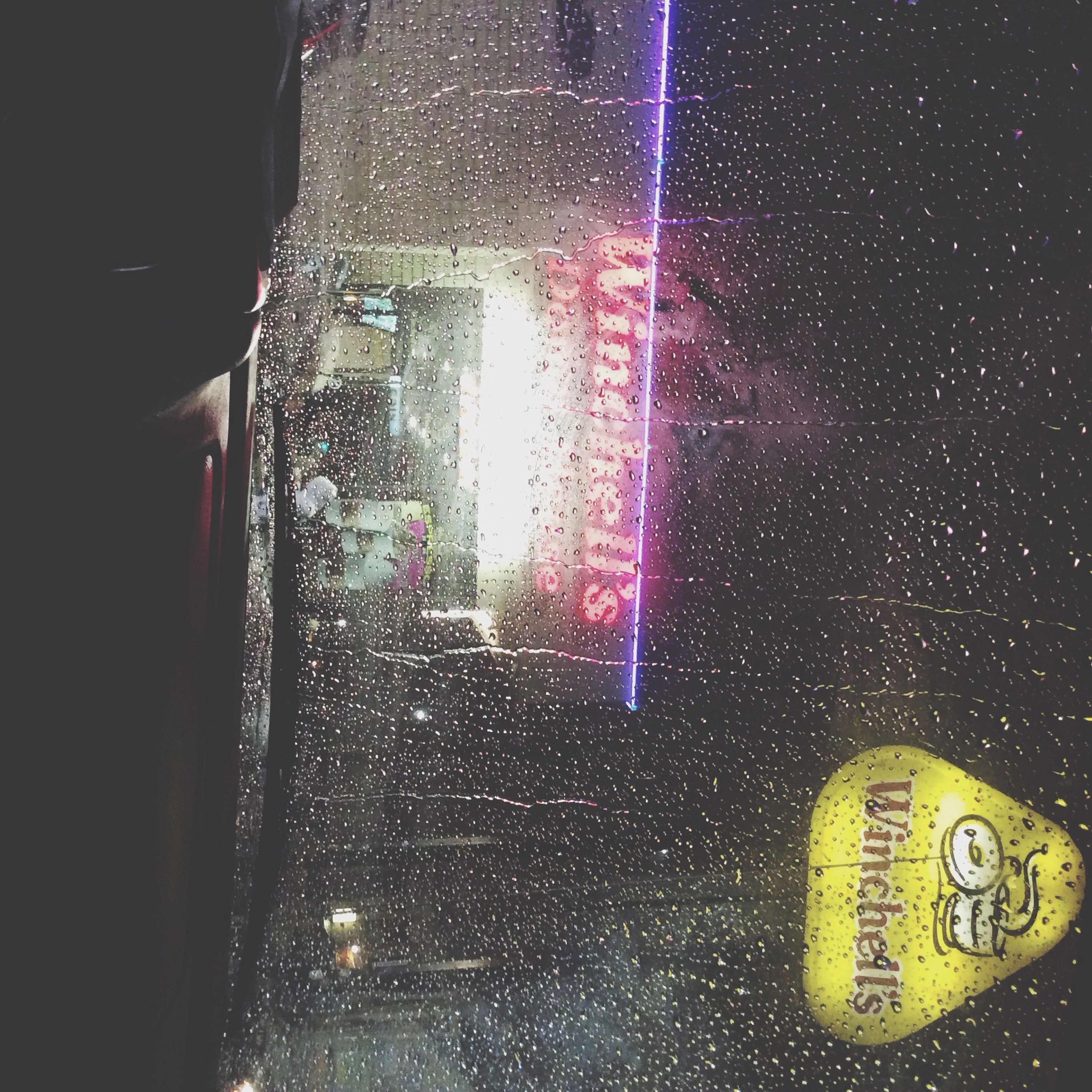 glass - material, indoors, transparent, illuminated, night, window, close-up, wet, drop, transportation, windshield, text, communication, vehicle interior, car, rain, western script, focus on foreground, car interior, glass