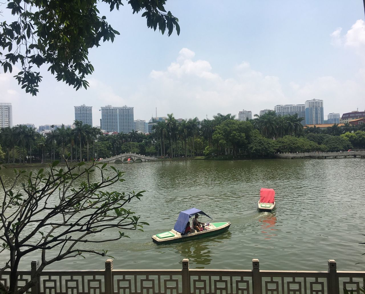 architecture, built structure, building exterior, tree, river, water, day, city, growth, sky, outdoors, skyscraper, cityscape, real people, nature, nautical vessel, urban skyline