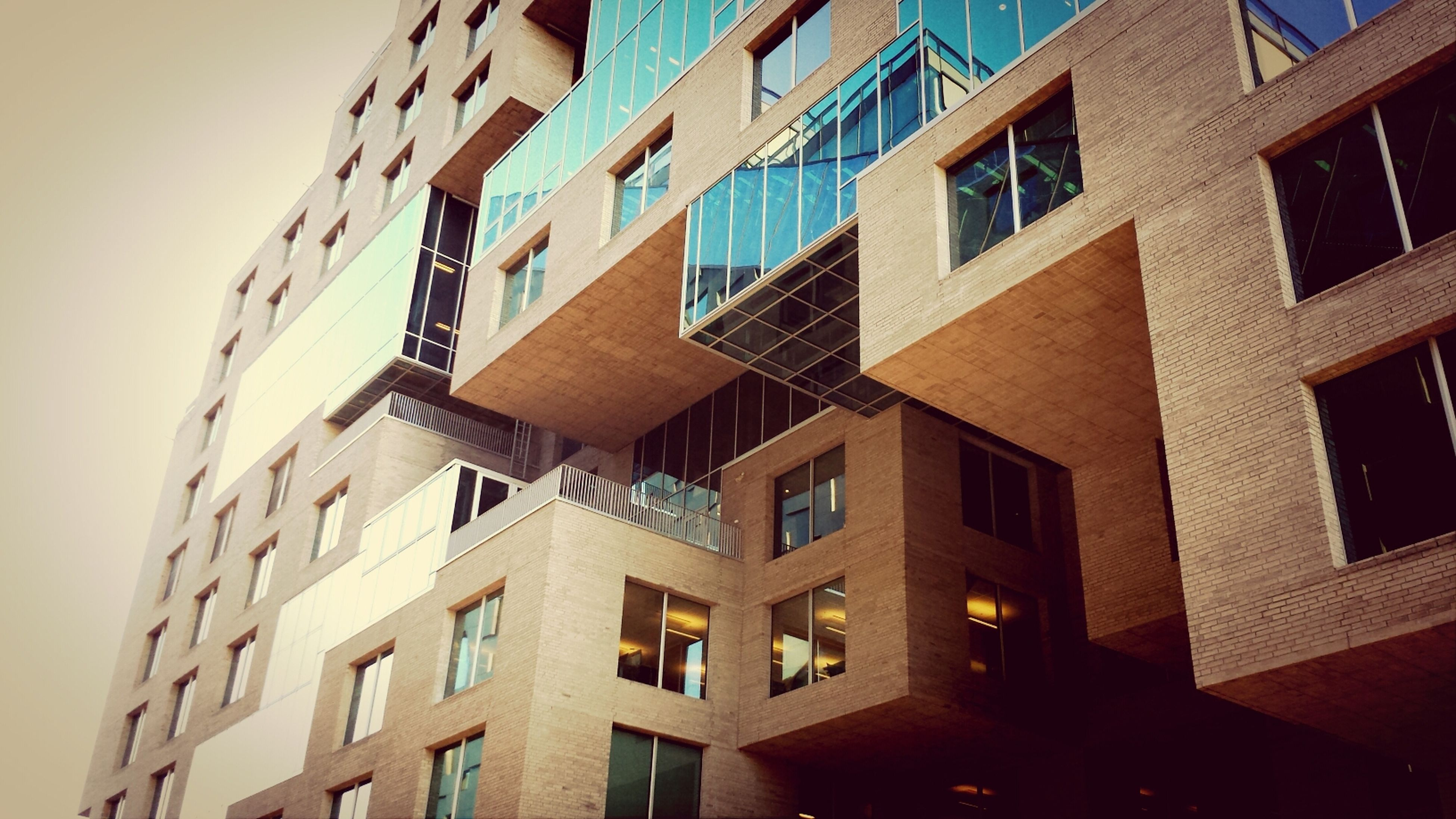 architecture, building exterior, built structure, low angle view, window, building, city, residential building, residential structure, apartment, modern, office building, balcony, repetition, day, clear sky, in a row, no people, outdoors, city life