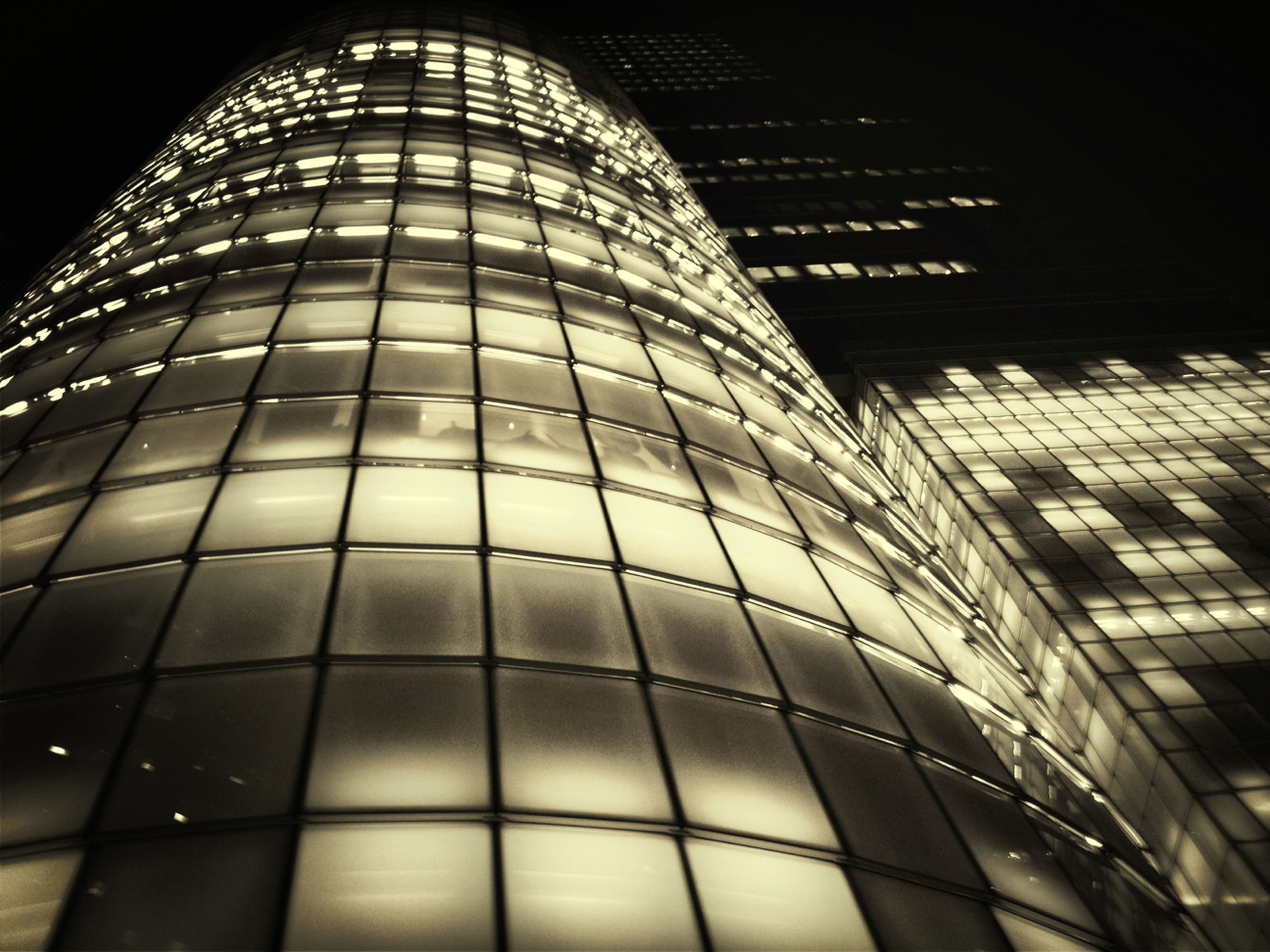 architecture, built structure, low angle view, modern, building exterior, office building, skyscraper, tall - high, city, night, illuminated, tower, glass - material, building, sky, reflection, pattern, architectural feature, no people, capital cities