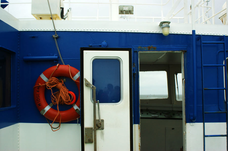Outside of a steel cabine and life jacket / lifesaver ring Captain Engine Room Blue Boat Captain Day Hanging Life Belt Life Buoy Life Jacket Lifesaver Lifesaver Ring No People Outdoors Red Rescue Safety Water Rescue