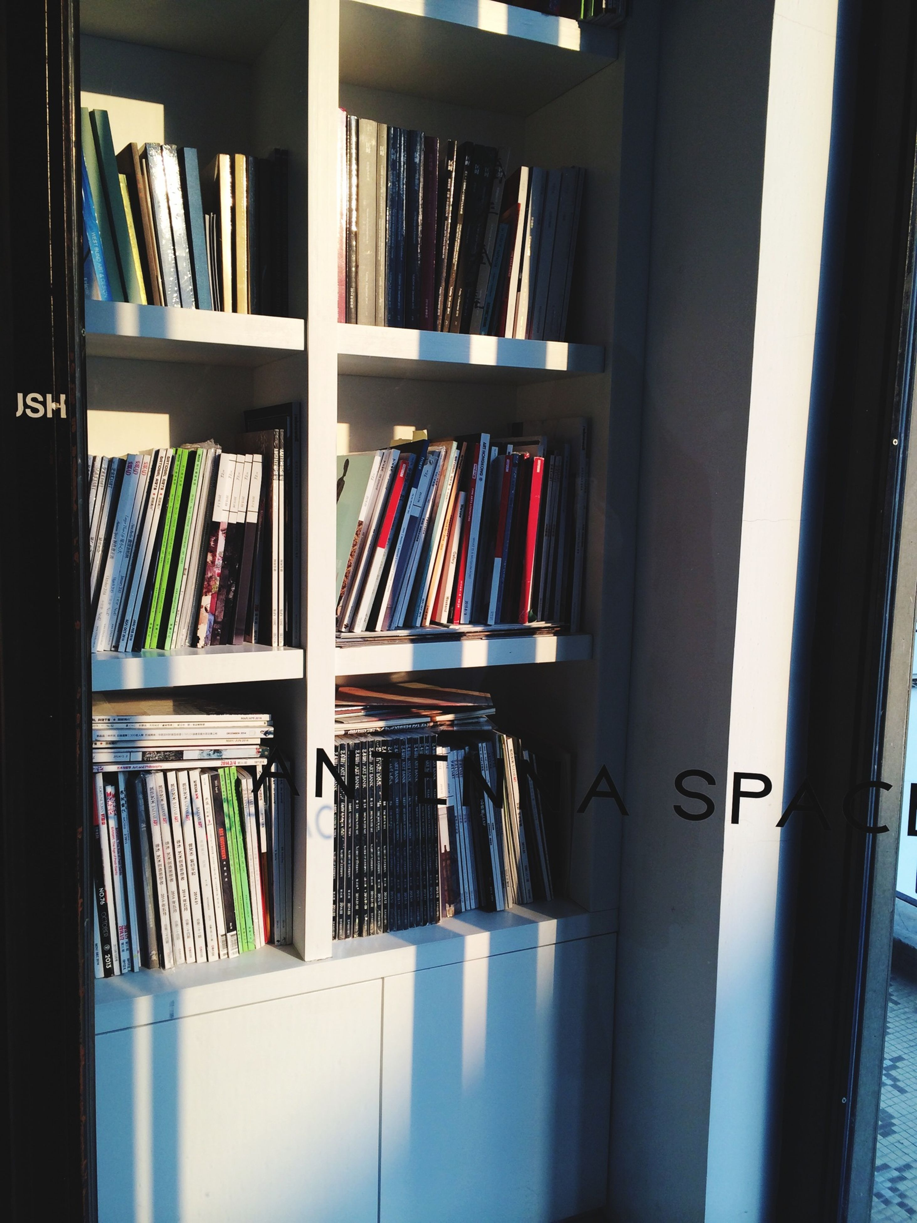 indoors, shelf, variation, bookshelf, book, large group of objects, arrangement, in a row, order, abundance, choice, education, multi colored, collection, window, library, home interior, still life, no people, desk