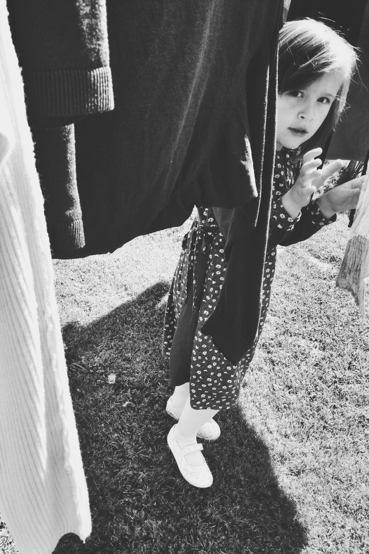 Girl Hiding Laundry Black And White Black & White Blackandwhite Photography Preschool Age Preschooler Looking Into The Camera Portrait Childhood Lifestyles Real People Outdoors Standing Dress The Portraitist - 2017 EyeEm Awards Live For The Story