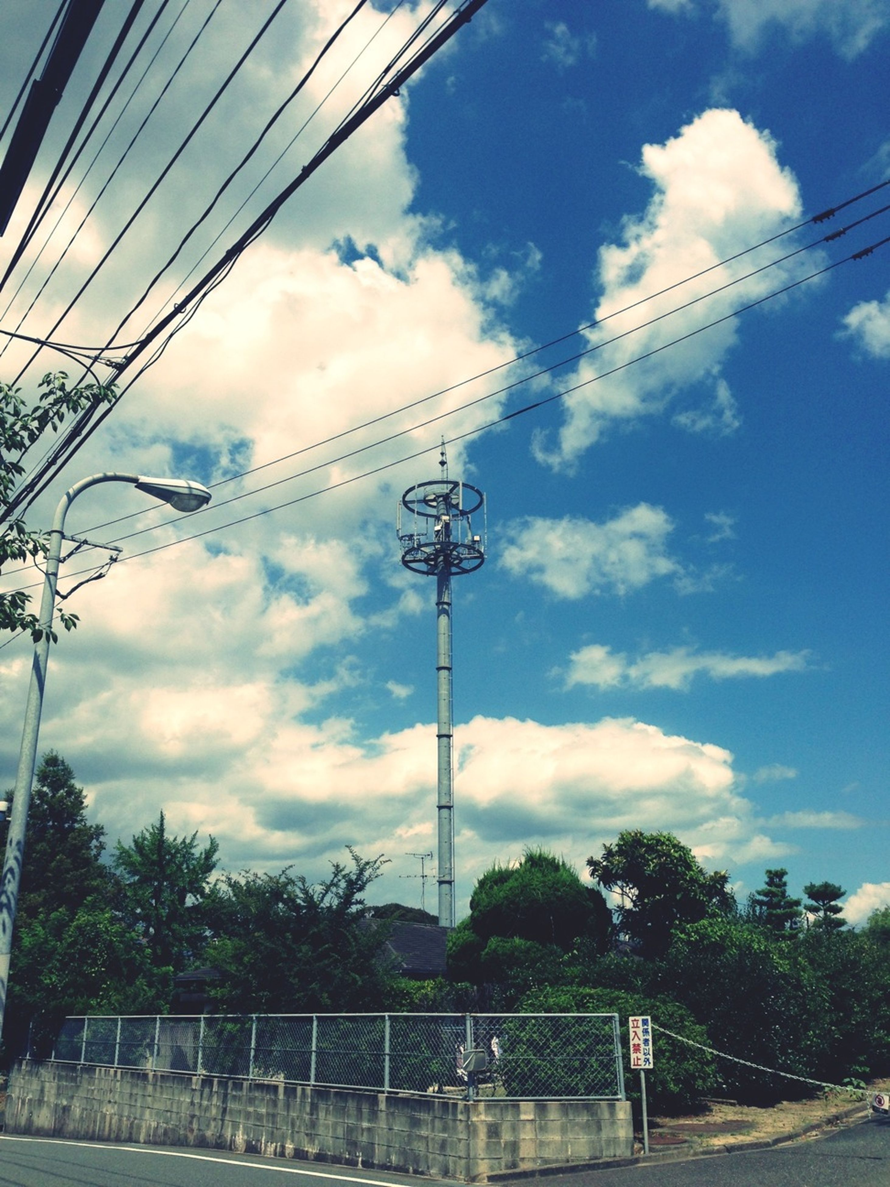 power line, electricity pylon, sky, cable, power supply, electricity, connection, cloud - sky, transportation, cloud, cloudy, fuel and power generation, power cable, street light, tree, low angle view, technology, mode of transport, railroad track, road