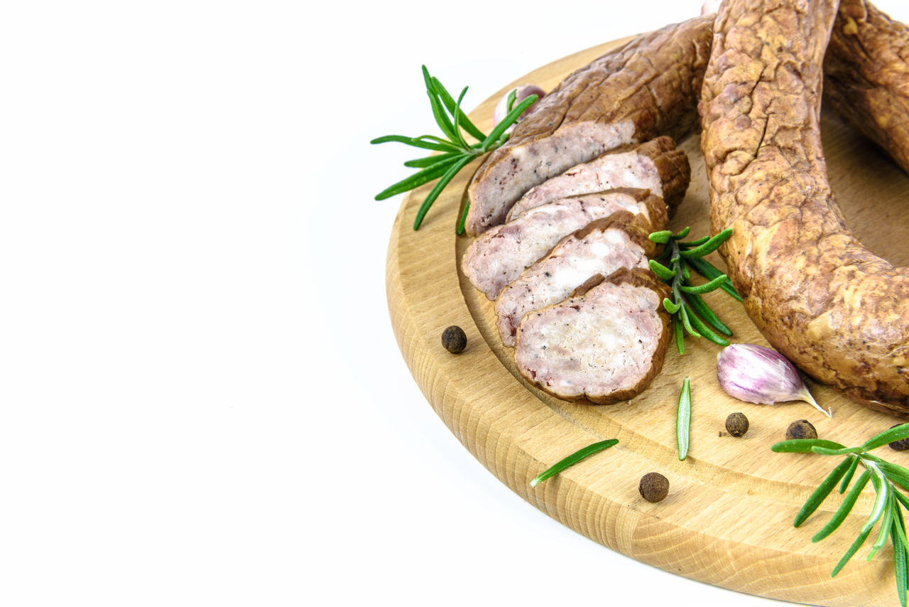 Traditional smoked sausage. Sliced sausage on a wooden board and rosemary, pepper and garlic on a white background. Aromatic Beef Food Fresh Garlic Gourmet Herbs Meat Meat! Meat! Meat! Overhead View Pepper Plate Pork Product Protein Rural Sausages Smoked Studio Shot Tasty White Background