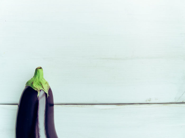 Fresh healthy eggplant on white wooden background. Additional space for text Agriculture Arranged Objects Aubergine Copy Space Diet Eggplant Fresh Gluten Free Healthy Lifestyle Kitchen Table Lines Minimalism Organic Food Organic Living Ripe Still Life Top View Of Food White Texture Wooden Texture