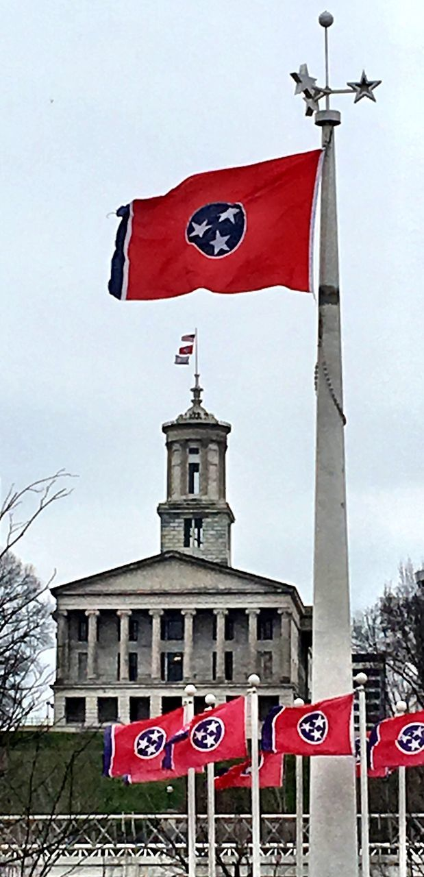 flag, red, patriotism, low angle view, text, pride, day, outdoors, architecture, building exterior, no people, sky