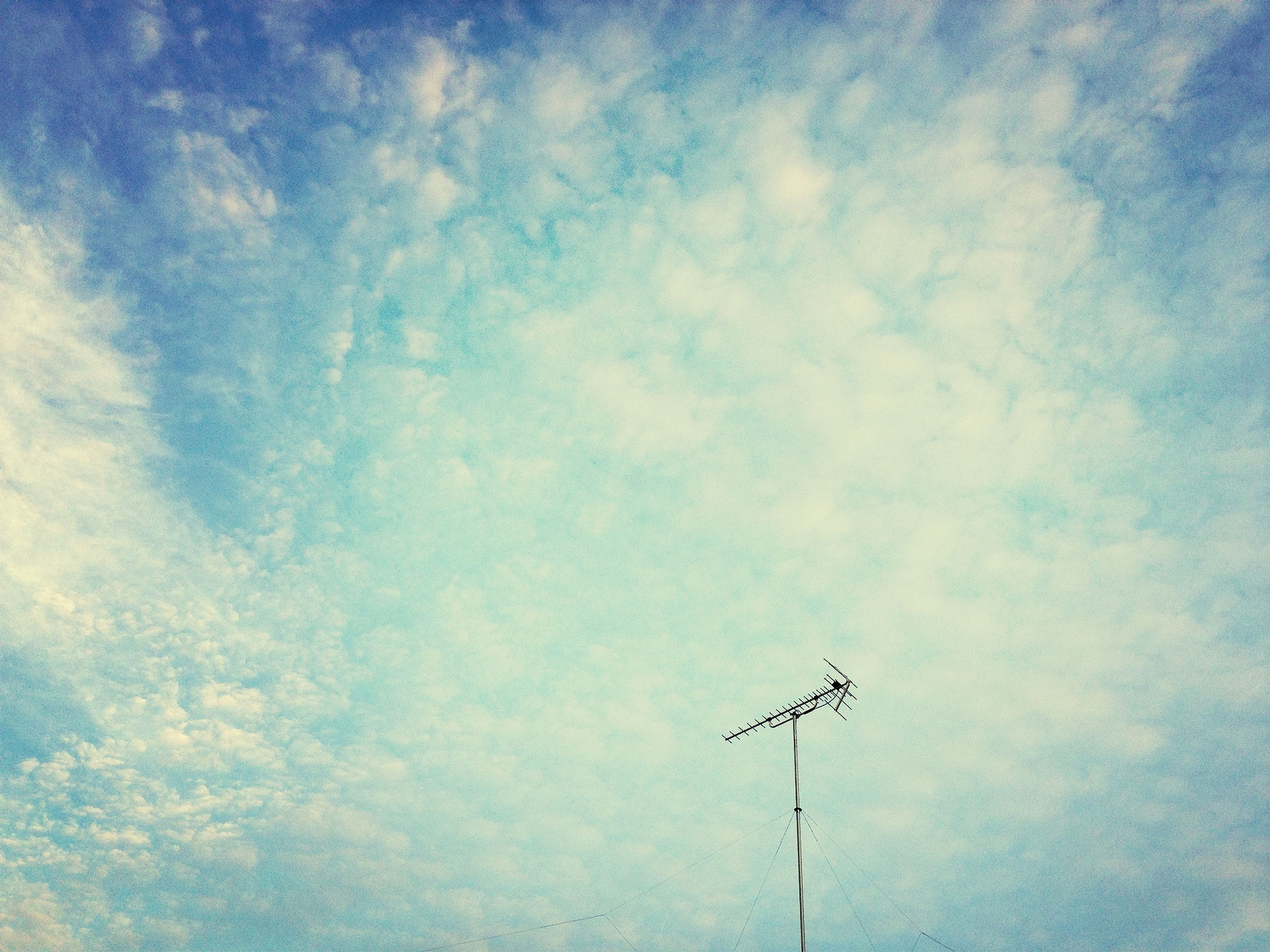 low angle view, sky, cloud - sky, blue, street light, cloudy, cloud, lighting equipment, technology, power line, nature, outdoors, day, electricity, no people, pole, high section, tranquility, silhouette, fuel and power generation