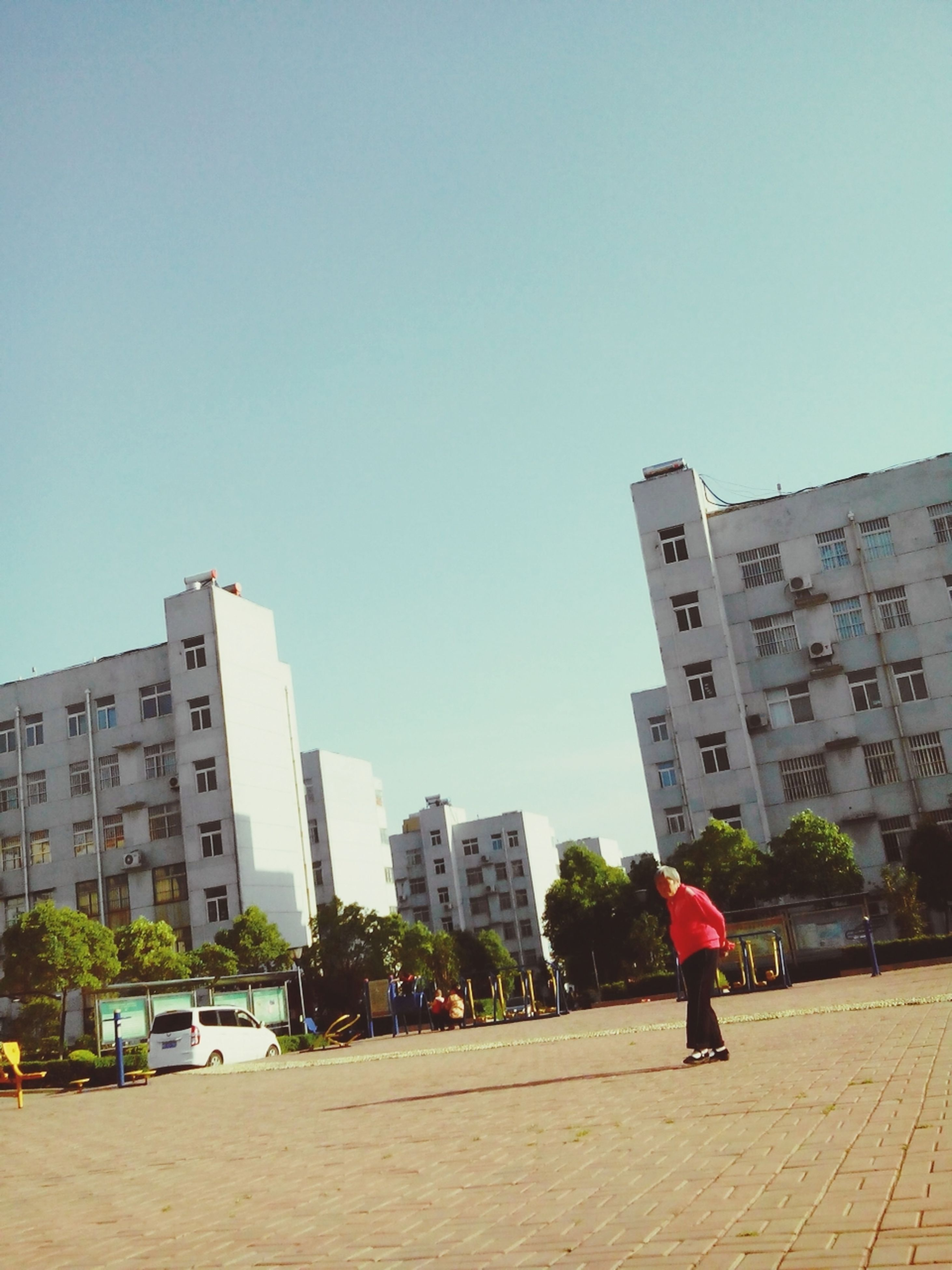building exterior, architecture, built structure, city, clear sky, street, walking, city life, building, copy space, tower, men, skyscraper, tall - high, road, residential building, day, cityscape