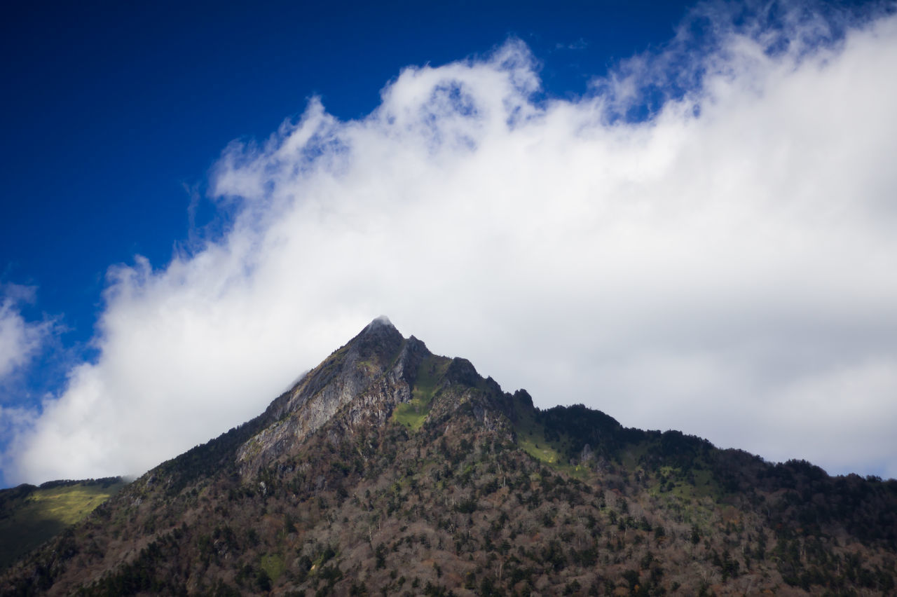Scenic View Of Majestic Mountain Against Cloudy Sky