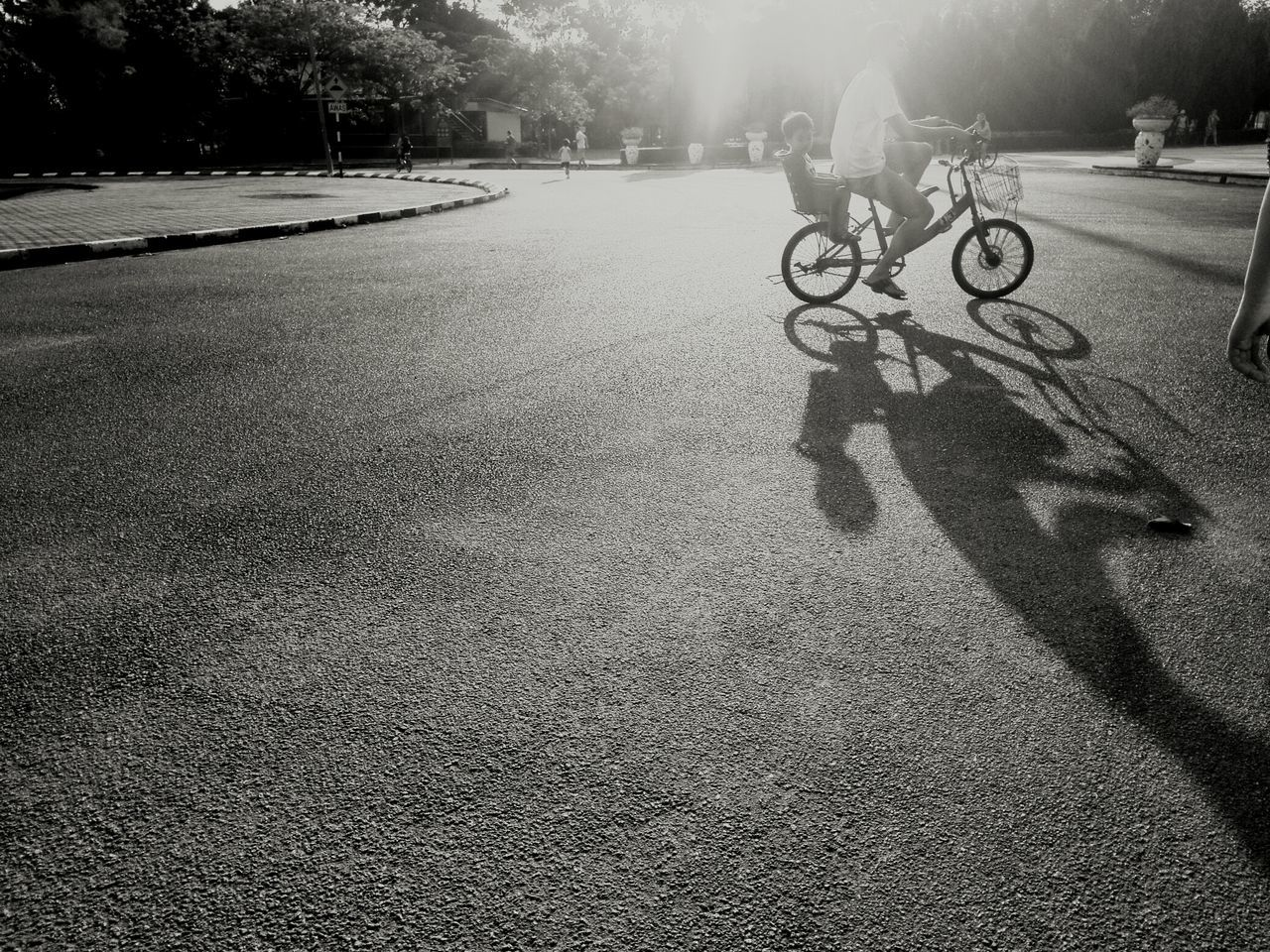 bicycle, transportation, outdoors, shadow, cycling, road, sunlight, riding, real people, land vehicle, day, bicycle rack, one person, tree, nature, people