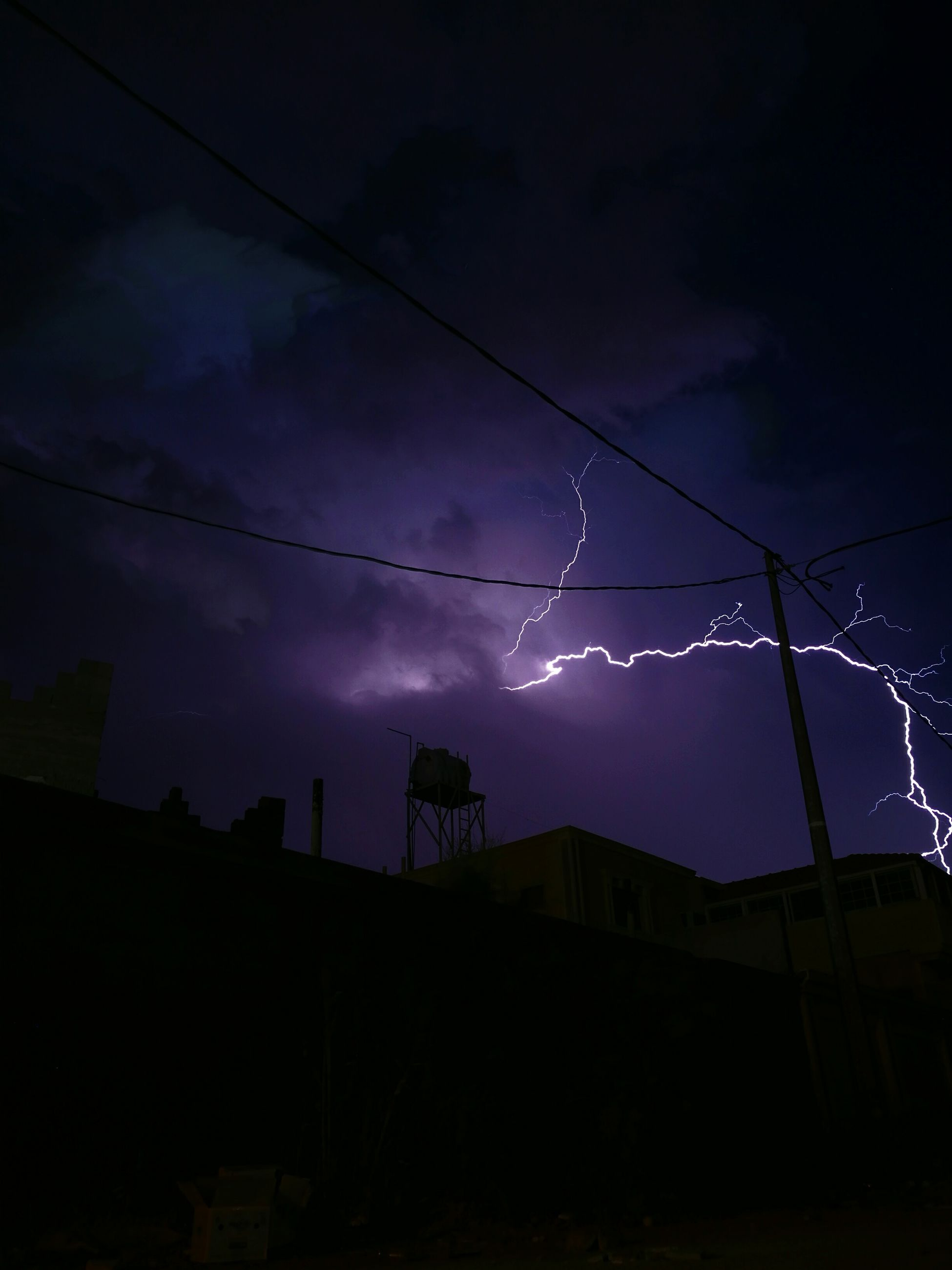 sky, night, dusk, electricity, cloud - sky, no people, low angle view, sunset, lightning, cable, illuminated, nature, outdoors, silhouette, electricity pylon, power line, tree, power supply, dramatic sky, storm cloud, built structure, beauty in nature, architecture, thunderstorm, forked lightning, power in nature