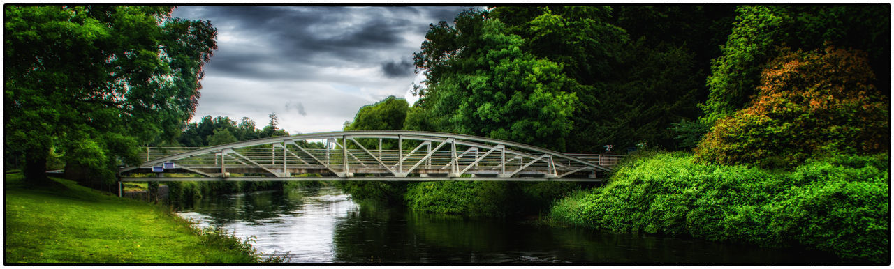 bridge - man made structure, connection, river, architecture, tree, built structure, water, bridge, outdoors, cloud - sky, day, sky, transportation, growth, no people, footbridge, nature, covered bridge