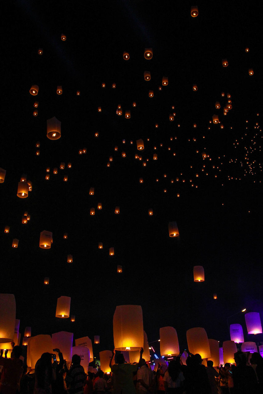 Low Angle View Of Illuminated Lanterns Flying In Sky At Night