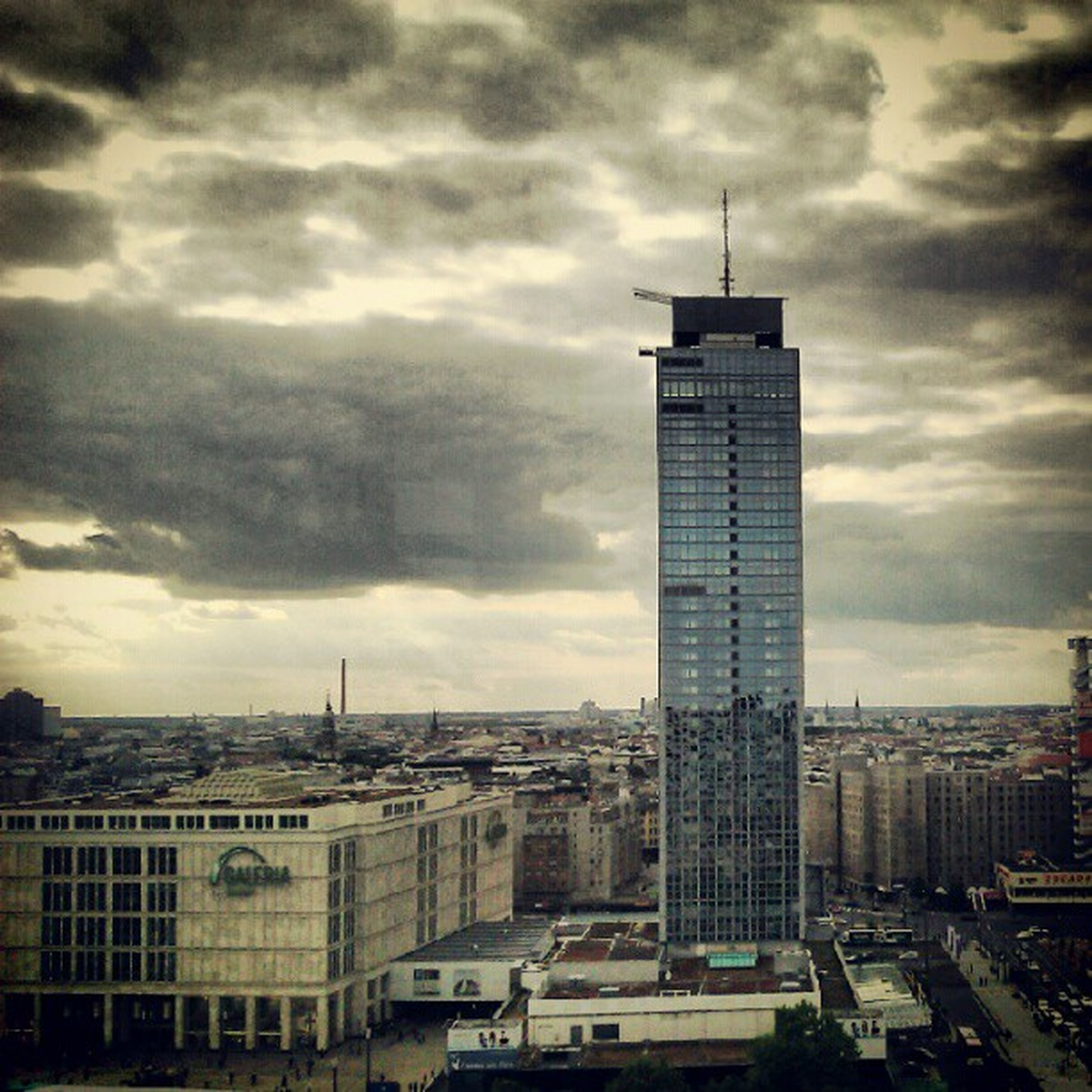 building exterior, architecture, built structure, sky, city, cloud - sky, cloudy, cityscape, skyscraper, tower, weather, tall - high, overcast, cloud, office building, modern, city life, building, residential building, storm cloud