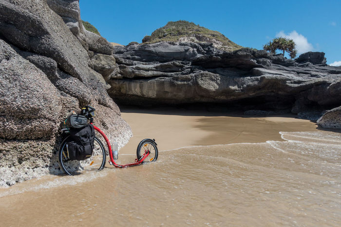 Kickbike with luggage on wave washed beach with rock outcroppings Adventure Beach Bicycle Coastline Day Escapism Kickbike Outdoors Rock Rock - Object Rock Formation Sand Sea Shore Stone Transportation Vacations Water