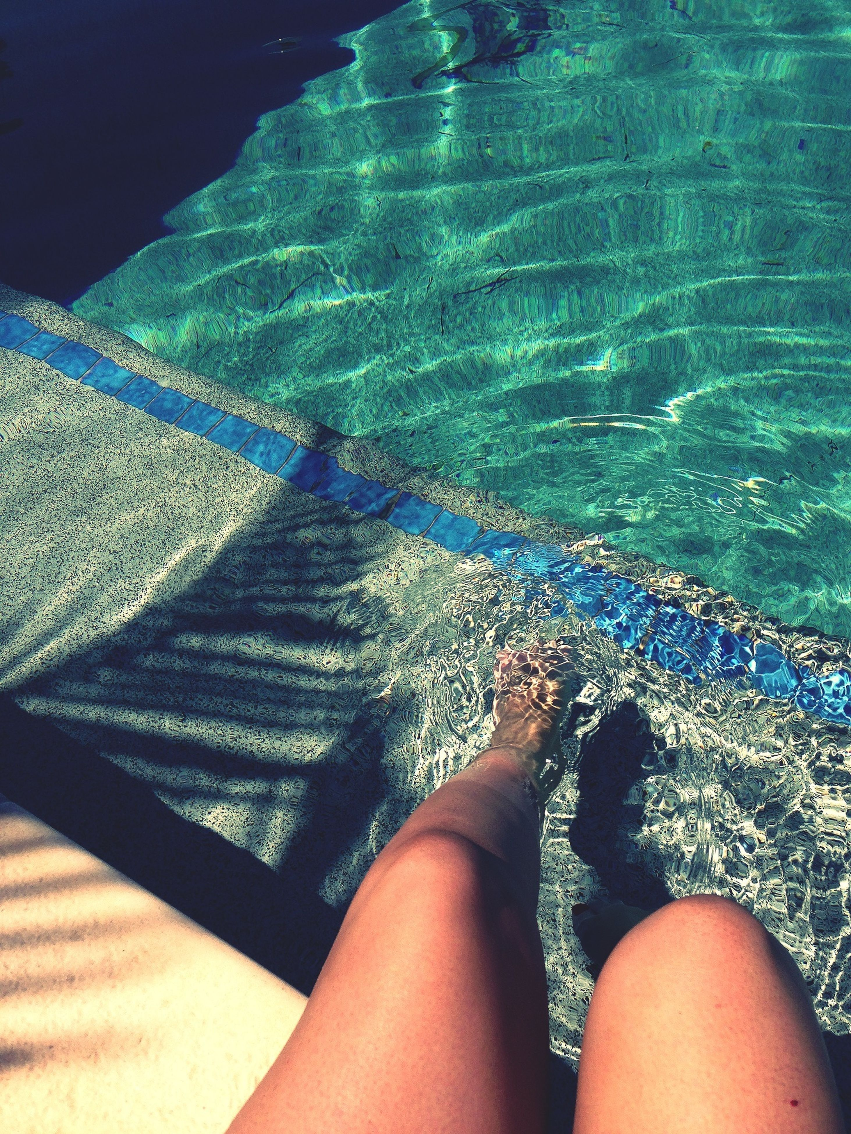 low section, person, personal perspective, water, barefoot, human foot, lifestyles, leisure activity, relaxation, high angle view, sea, vacations, relaxing, swimming pool, legs crossed at ankle, sunlight