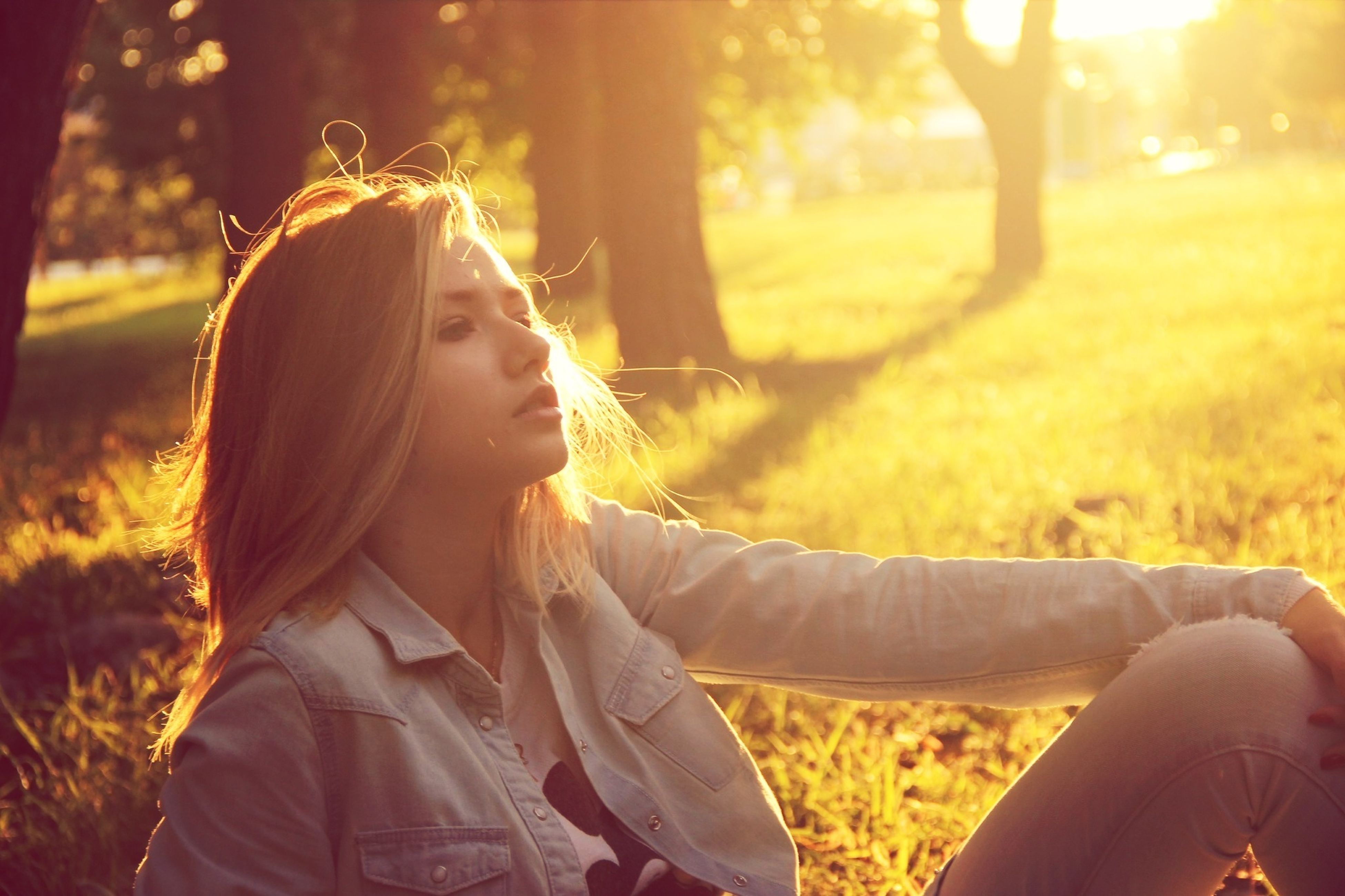 lifestyles, leisure activity, focus on foreground, tree, casual clothing, headshot, person, young adult, young women, long hair, sunlight, field, rear view, nature, park - man made space, outdoors, standing
