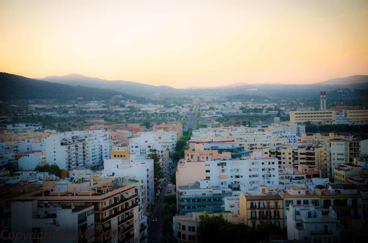 architecture, cityscape, building exterior, city, sunset, built structure, no people, outdoors, mountain, sky, clear sky, residential building, town, residential, nature, day, city location