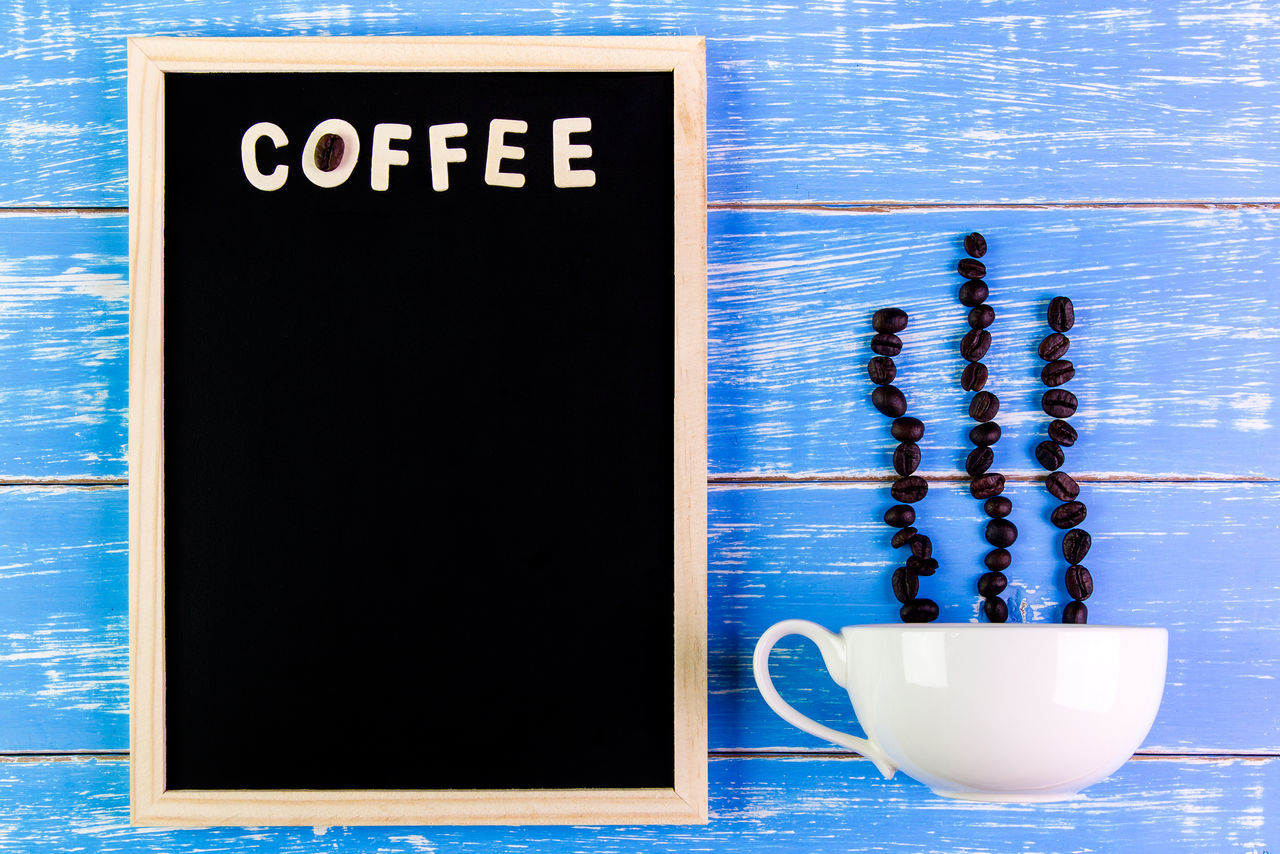 Roasted Coffee Beans By Cup With Text On Blackboard At Wooden Table