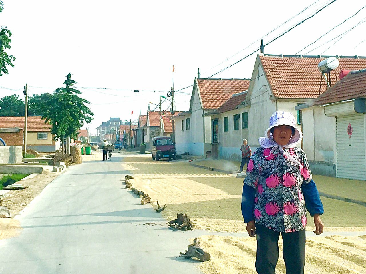 Village life in a rural countryside in northern China Street Road Village Life Woman Hat Wearing Hat Farmhouses Power Lines Electrical Poles Rural Urban Countryside Travel Shandong China Culture Grains Wheat Wheat Drying On Street Colour Of Life People And Places