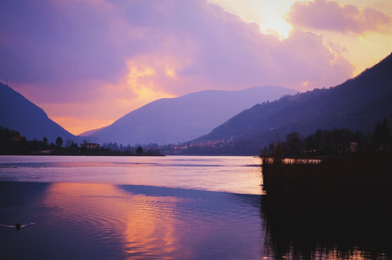 Scenic View Of Lake And Mountains During Sunset