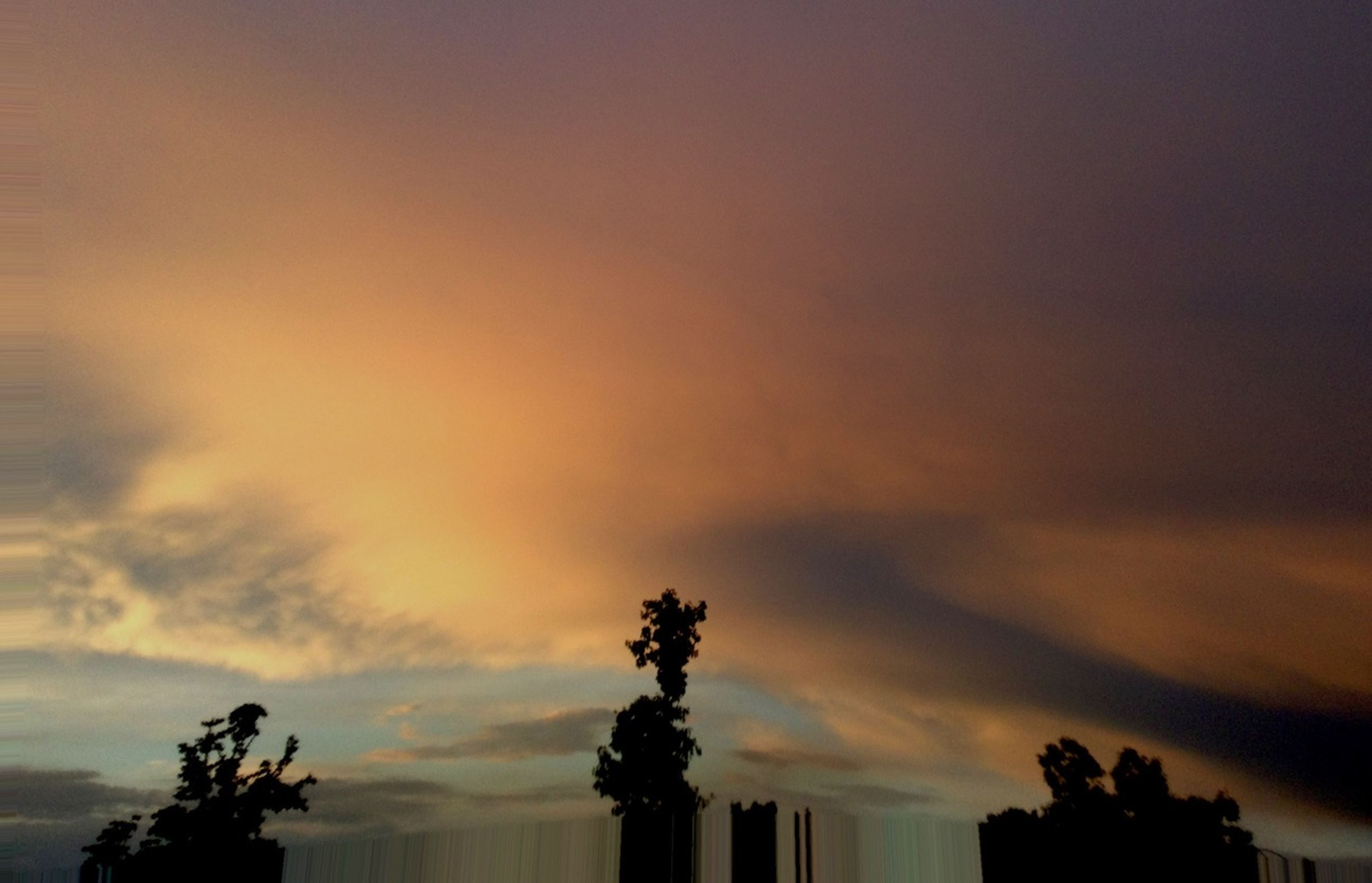 sky, low angle view, sunset, silhouette, cloud - sky, tree, built structure, architecture, cloudy, building exterior, beauty in nature, nature, scenics, dusk, cloud, tranquility, high section, outdoors, weather, tranquil scene