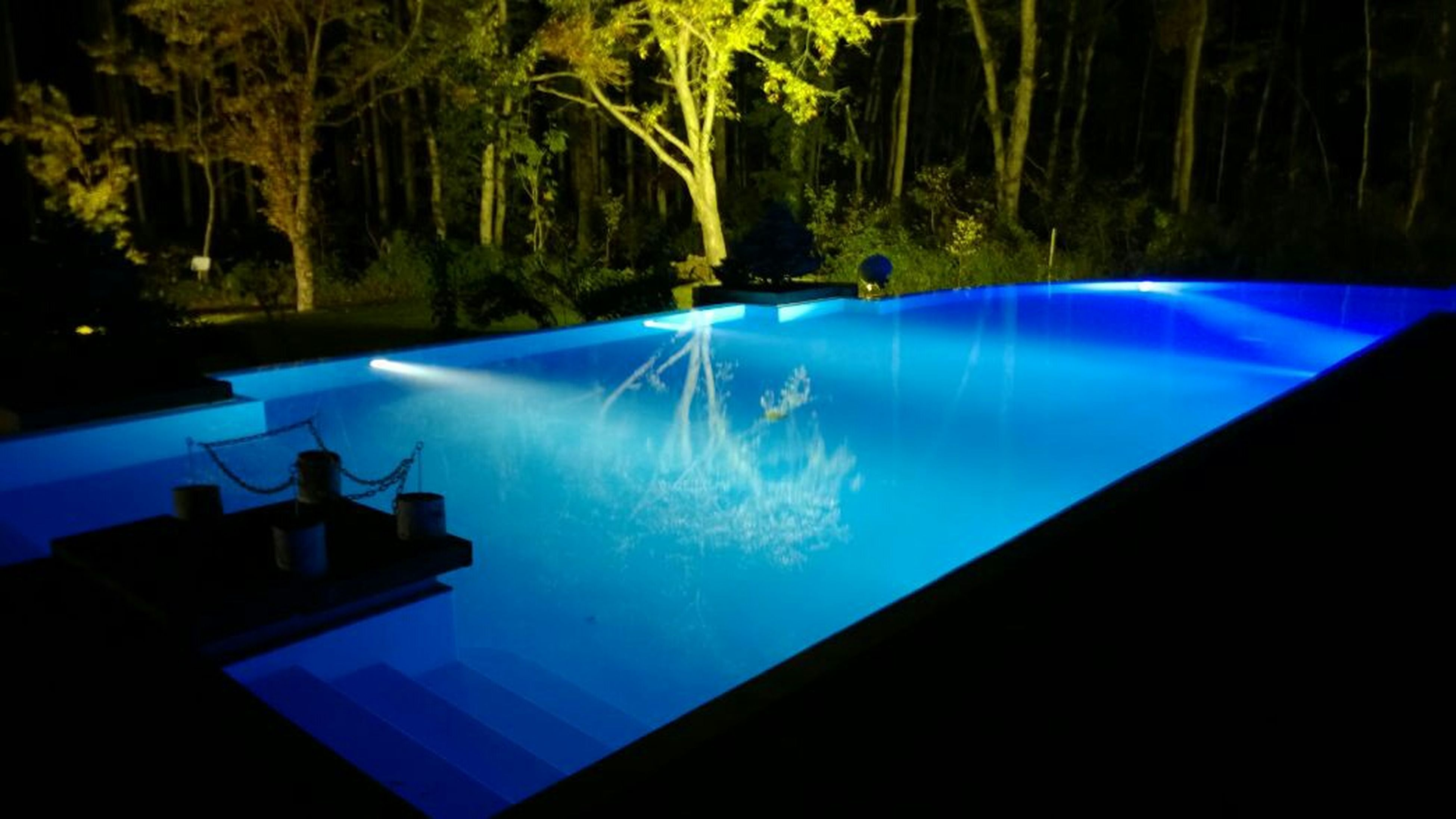 blue, water, tree, beauty in nature, nature, night, swimming pool, scenics, tranquility, no people, illuminated, tranquil scene, green color, turquoise colored, outdoors, growth, reflection, idyllic, purple, high angle view