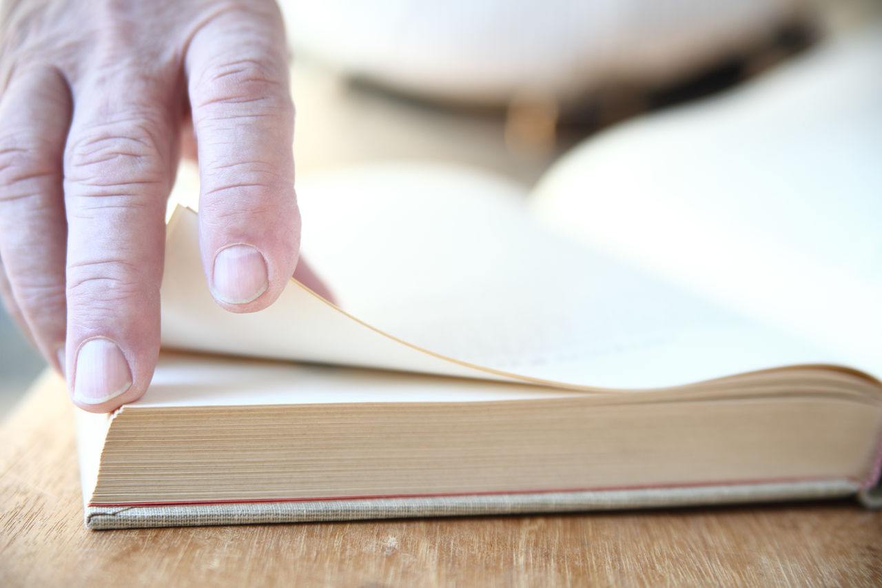 A man turns the pages of a large book. Book Closeup Education Fingers Hand Indoors  Information Learning Literacy Literature Man Natural Light Pages Reading A Book Researching Senior Studying Text Space Turning Unrecognizable Person Wood Surface