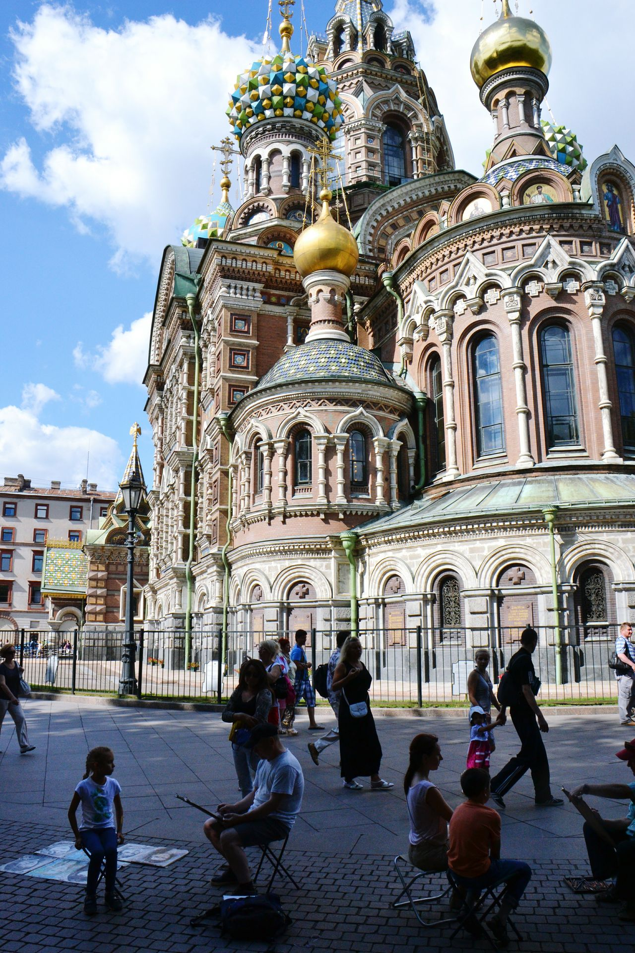 Church of Savior on the Blood in St. Petersburg, Russia; with sketch artists doing portraits in foreground. Religion Architecture Travel Destinations Spirituality Place Of Worship Tourism Travel Vertical Building Exterior Built Structure Dome Large Group Of People Gold Colored Sky Outdoors Façade Men