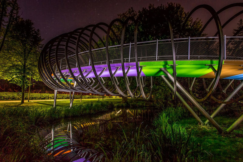 "Die Rehberger Brücke ""Slinky springs to fame"" in Oberhausen Architecture Foodbridge Industry Oberhausen Reflection Rehberger Brücke SLINKY SPRINGS TO FAME Tobias Rehberger Bridge Illuminated Industrial Culture Lightdrawing Long Exposure Night No People Outdoors Steel Tree"
