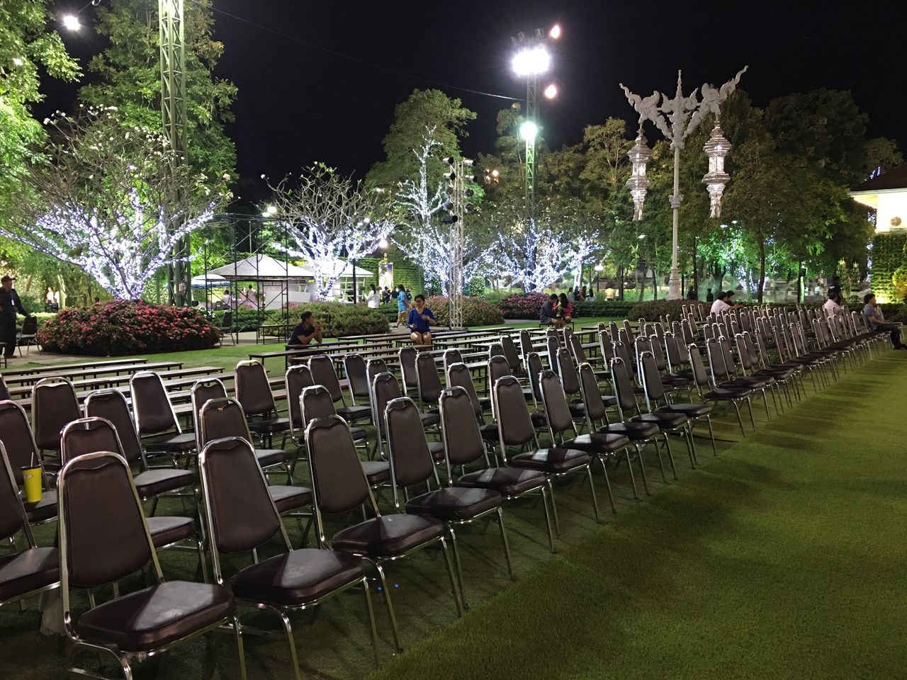 in a row, night, tree, grass, chair, outdoors, no people, illuminated, nature