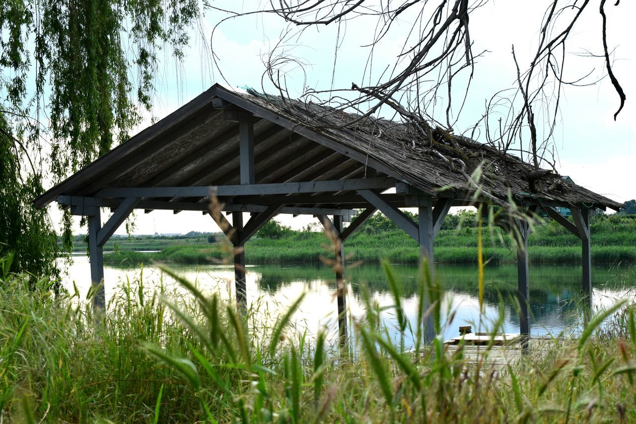 built structure, water, architecture, outdoors, nature, day, lake, tree, no people, roof, grass, covered bridge, beauty in nature, sky